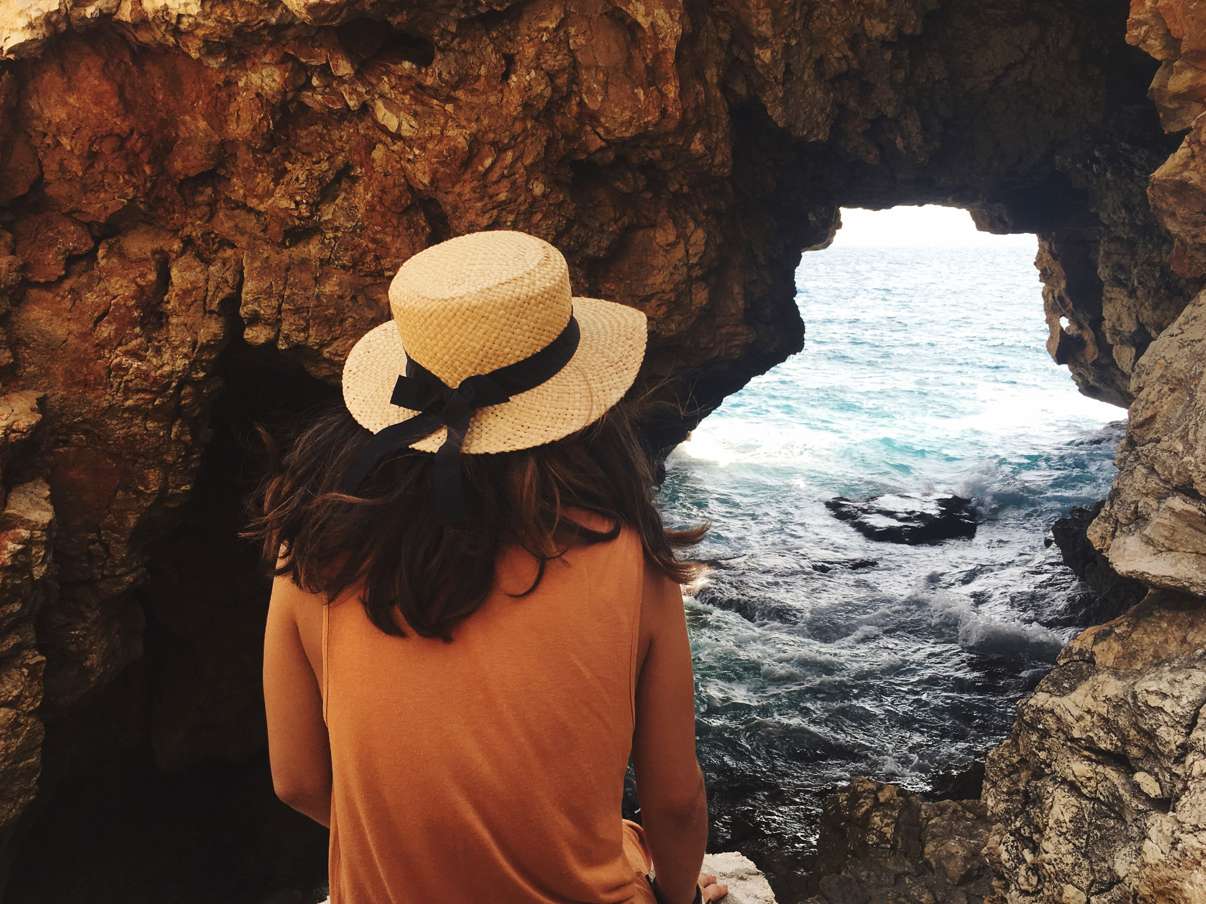 standing, hat, water, person, obscured face, front view, sea, in front of, mask - disguise, rock formation, nature, outdoors, scenics, tranquility