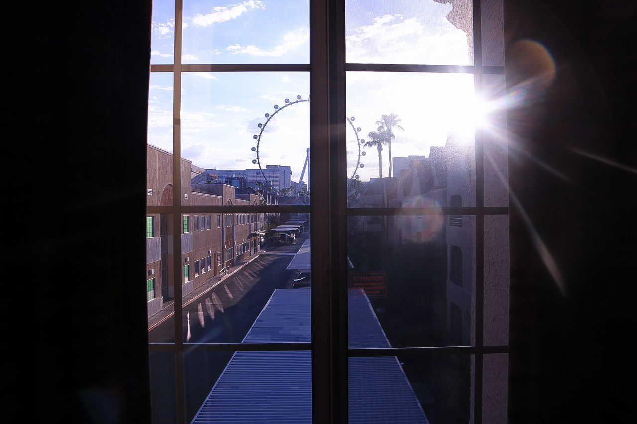 window, lens flare, glass - material, sunlight, sun, sunbeam, sky, indoors, day, built structure, reflection, silhouette, architecture, rail transportation, transportation, looking through window, cloud - sky, train - vehicle, public transportation, building exterior, no people, mountain, city, nature