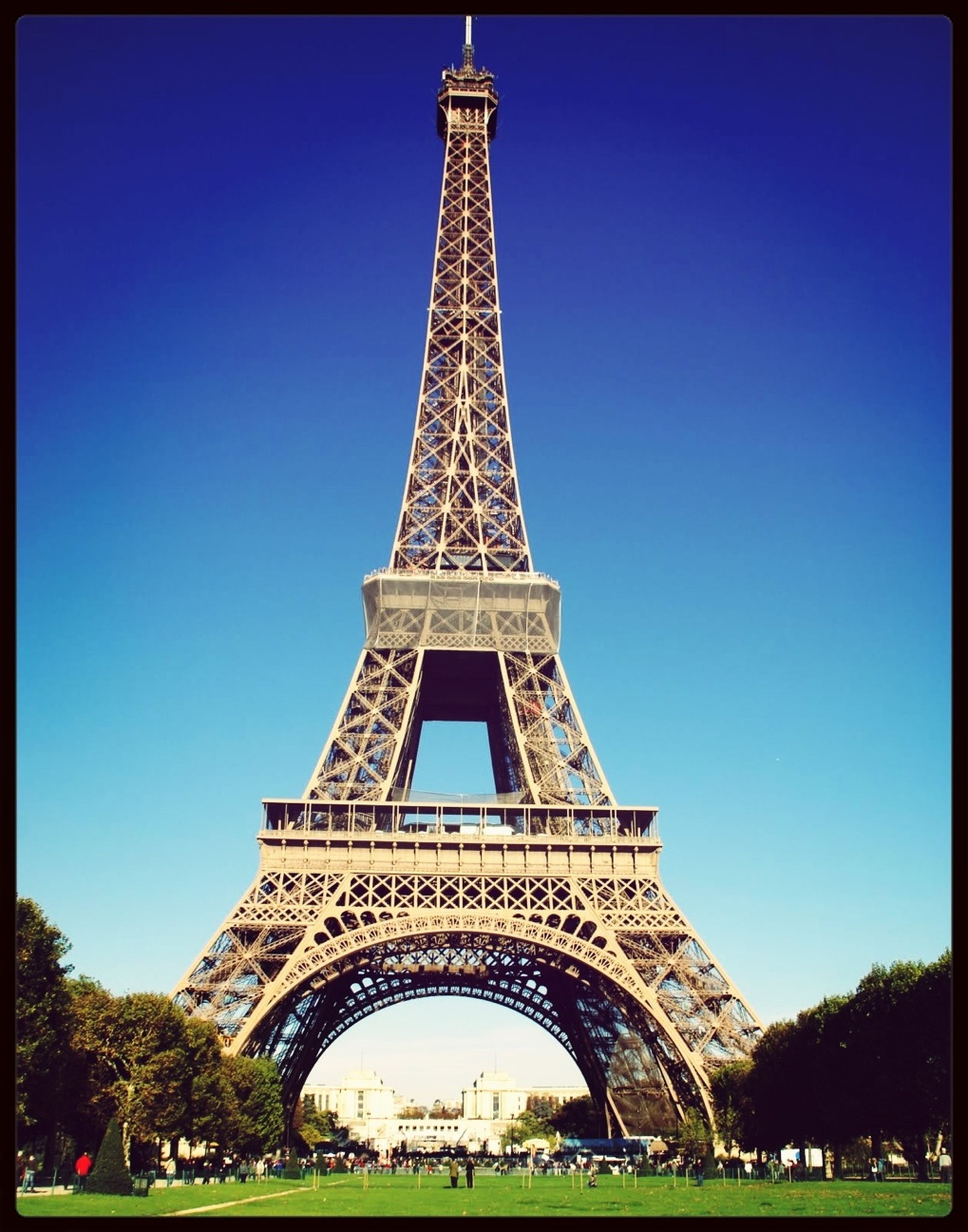 eiffel tower, clear sky, famous place, architecture, built structure, international landmark, travel destinations, tourism, tower, culture, capital cities, travel, history, tall - high, tree, low angle view, metal, transfer print, monument, architectural feature