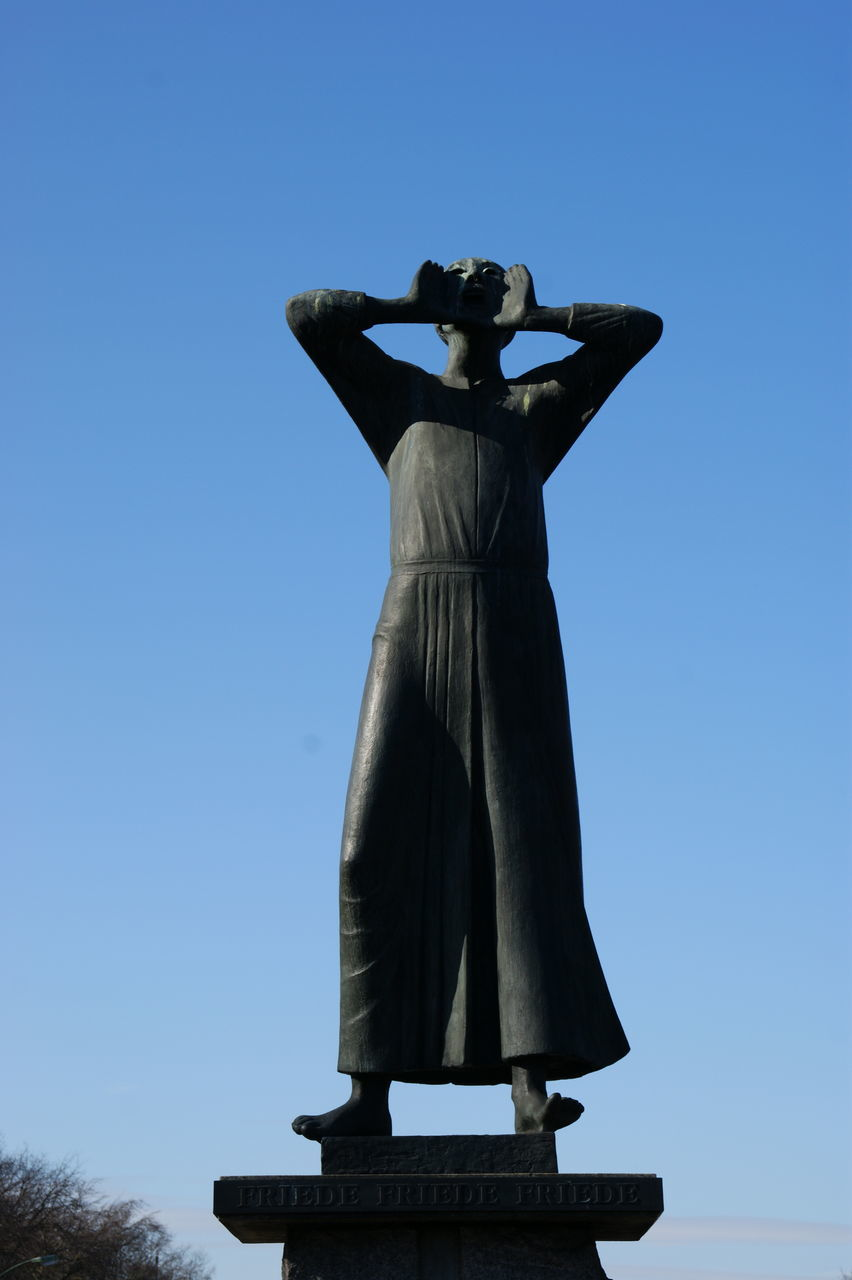 clear sky, full length, standing, day, low angle view, rear view, outdoors, statue, sky, one person, sculpture, real people, people