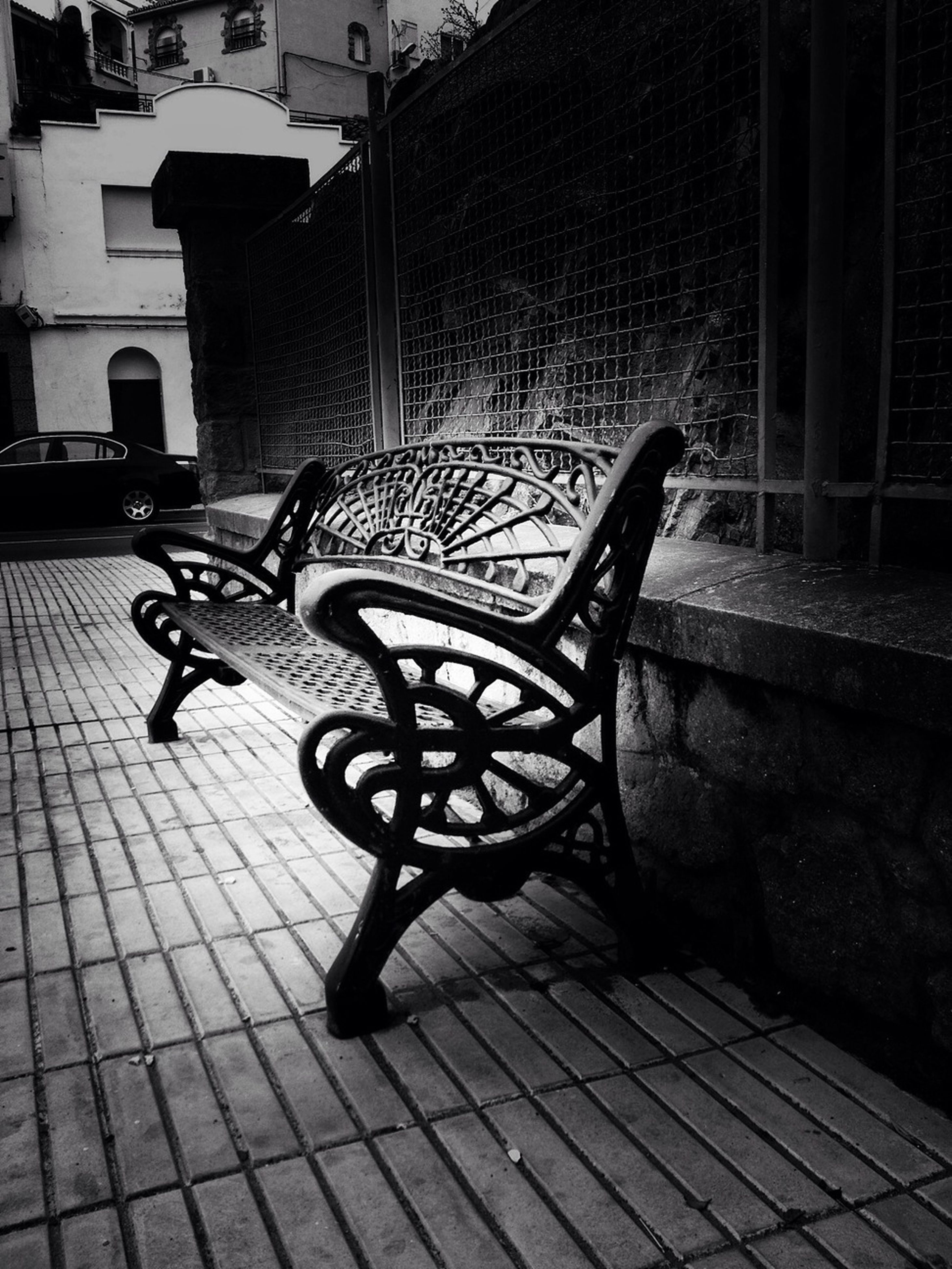 chair, absence, empty, built structure, cobblestone, building exterior, architecture, sidewalk, seat, bench, shadow, table, no people, paving stone, sunlight, flooring, day, wall - building feature, outdoors, tiled floor