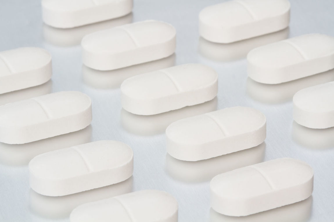 Rows of white, pain relief tablets, pills and drugs on an isolated background. Science research and drug production image. Antibiotics Aspirin Chemistry Chemistry Lab Dosage Dost Drugs In A Row Lines Overdose Overused  Pain Pain Relief PainKiller Painkilling Paracetamol Pharmaceuticals  Pharmacy Pills Research Rows Scenics Scientific Tablet White