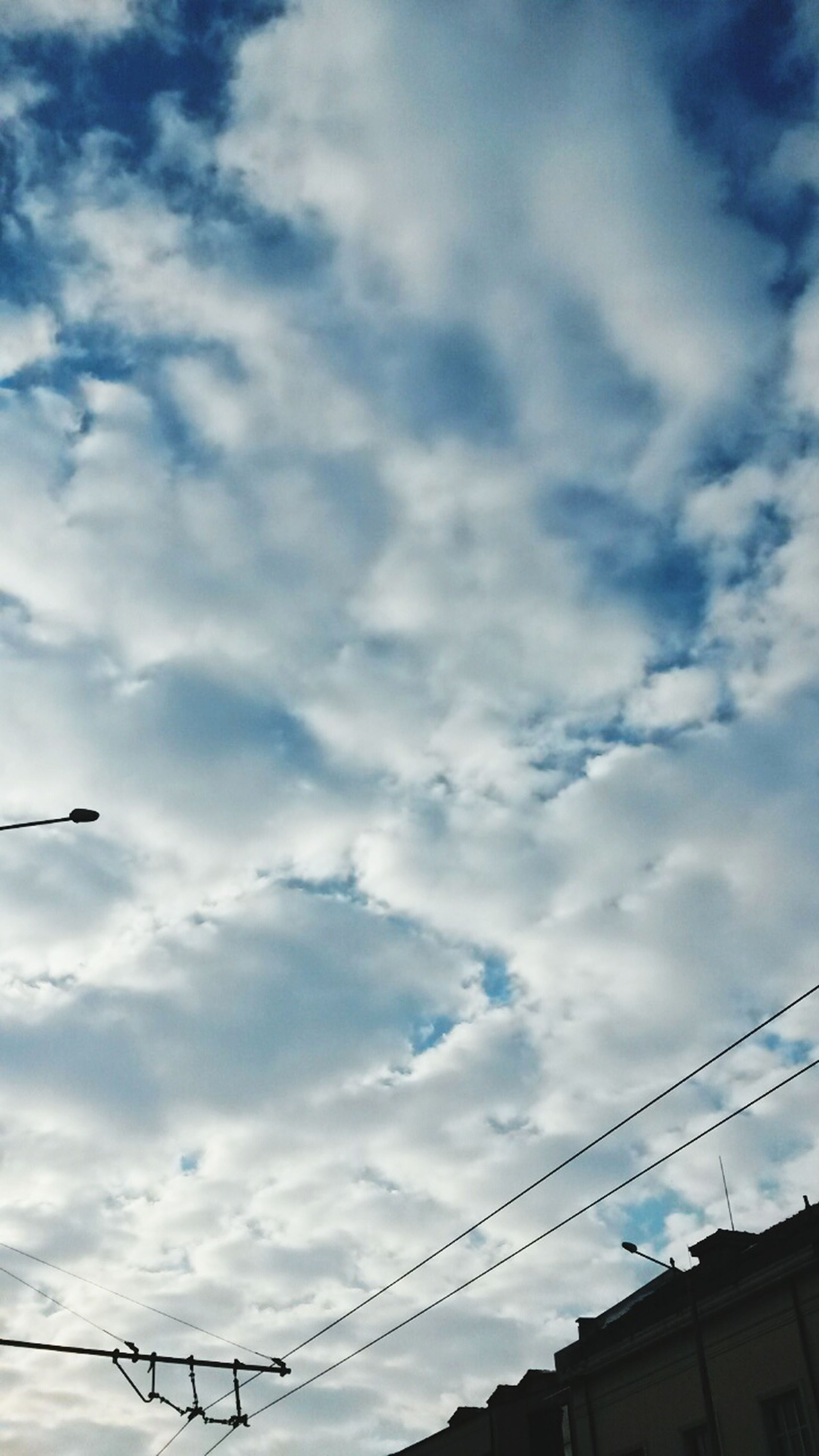 low angle view, power line, sky, connection, cable, cloud - sky, electricity pylon, electricity, power supply, cloudy, cloud, built structure, architecture, silhouette, power cable, bird, technology, building exterior, fuel and power generation, outdoors