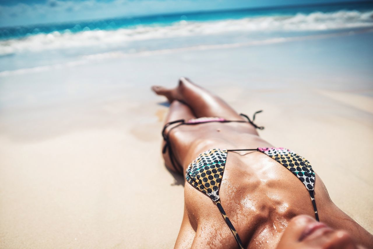 Tanning Beach Sand Sea One Person Real People Water Shore Leisure Activity Lifestyles Nature Summer Bikini Vacations Day Hapiness Relaxing Close-up Human Body Part Sky Woman Holidays Summertime Summer Bikini