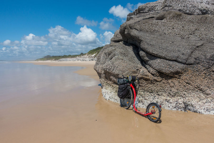 Kickbike with luggage on wave washed beach with rock outcroppings Adventure Beach Bicycle Cliff Coastline Day Escapism Geology Getting Away From It All Horizon Over Water Kickbike Outdoors Recreational Pursuit Rock Rock - Object Rock Formation Sand Sea Shore Tranquil Scene Vacations