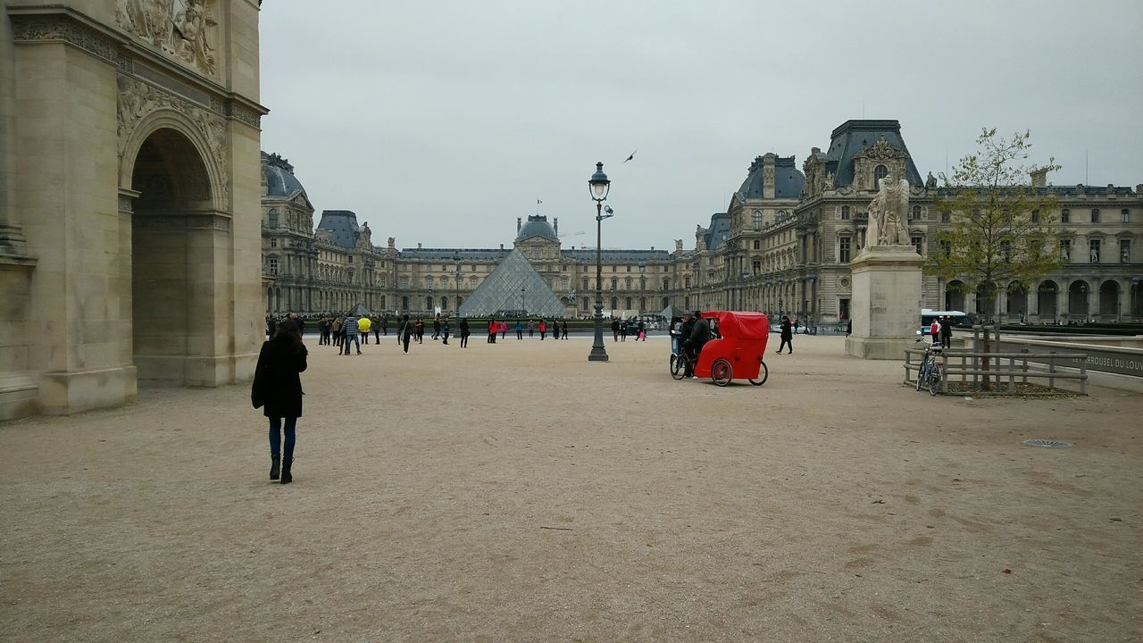 Walking towards, Waiting at the Louvre. · Paris France Paris ❤ Louvre Museum Louvre Pyramid Culture History Landmark Tourism Sightseeing Travel Destinations Discovery Architecture Urban Landscape City Life Gray Sky Cloudy Day