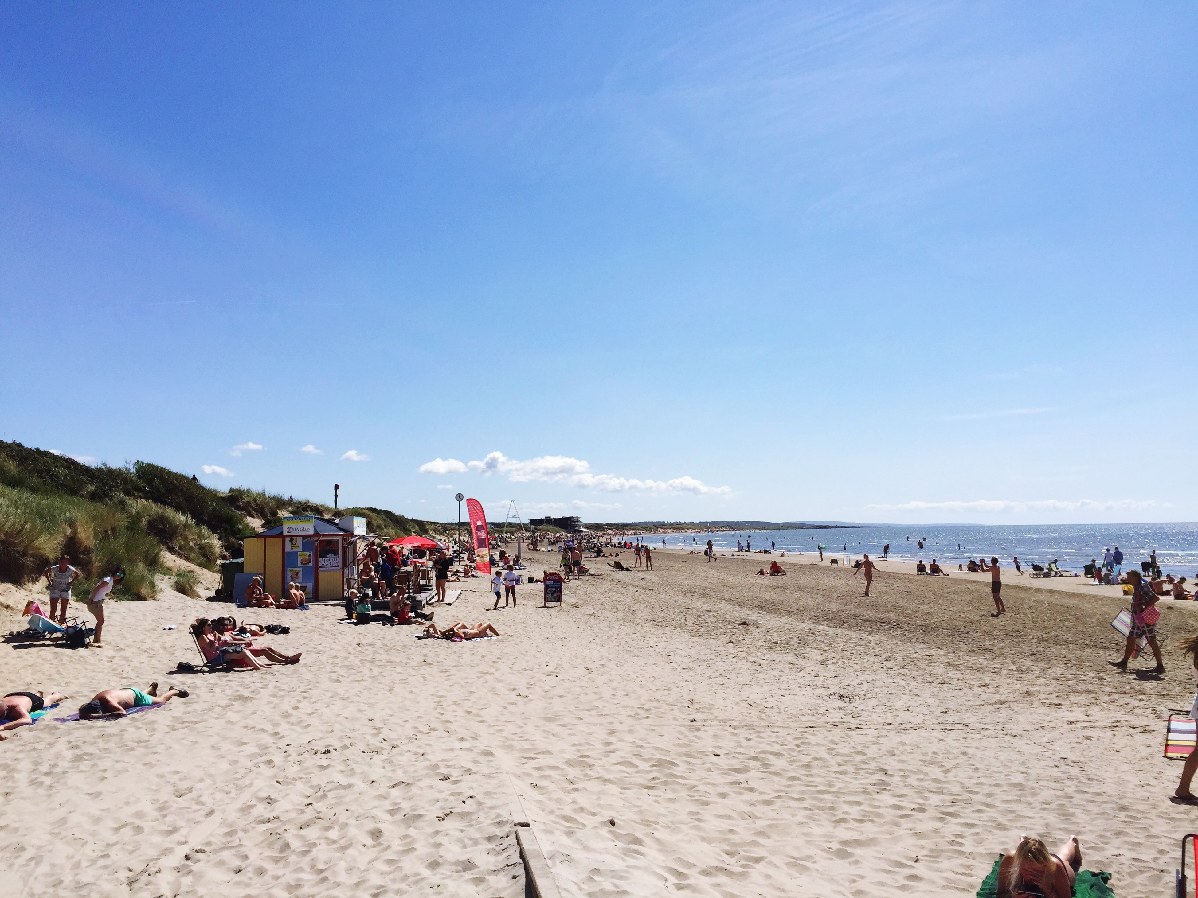 beach, sea, large group of people, water, sand, shore, vacations, leisure activity, horizon over water, lifestyles, person, mixed age range, sky, men, blue, tourist, relaxation, scenics, beach umbrella