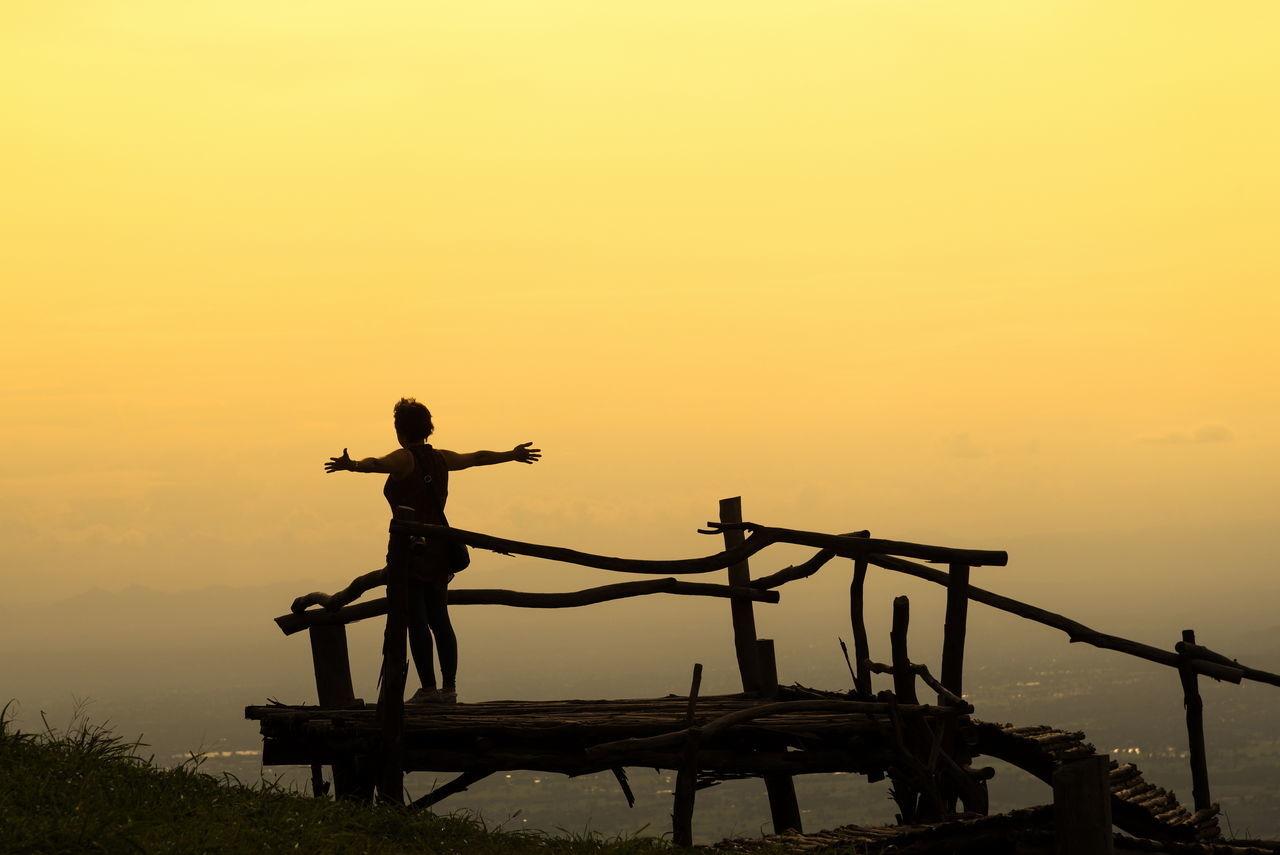 sunset, silhouette, orange color, nature, outdoors, real people, standing, lifestyles, sky, one person, beauty in nature, scenics, men, full length, day, people
