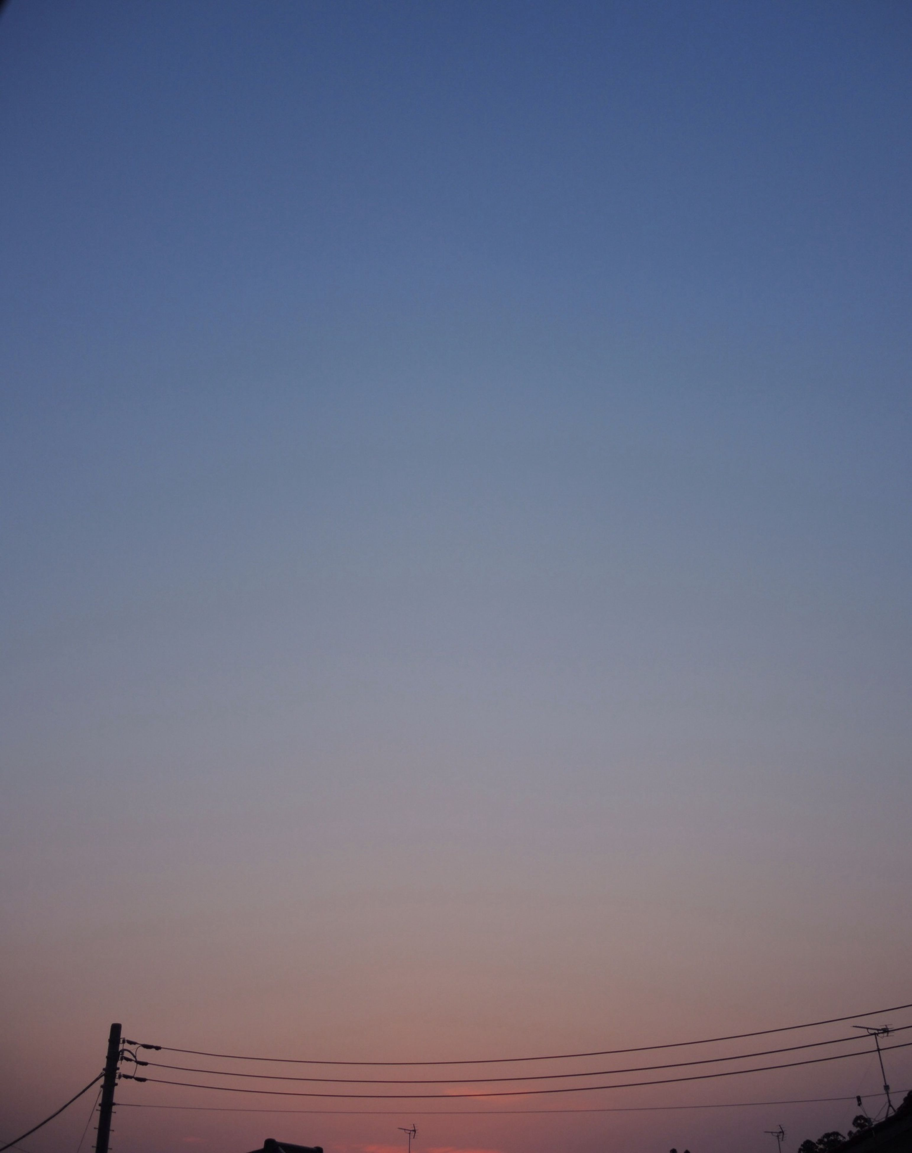 clear sky, silhouette, sunset, copy space, low angle view, tranquility, blue, scenics, nature, tranquil scene, beauty in nature, dusk, sky, connection, outdoors, power line, no people, idyllic, orange color, electricity pylon