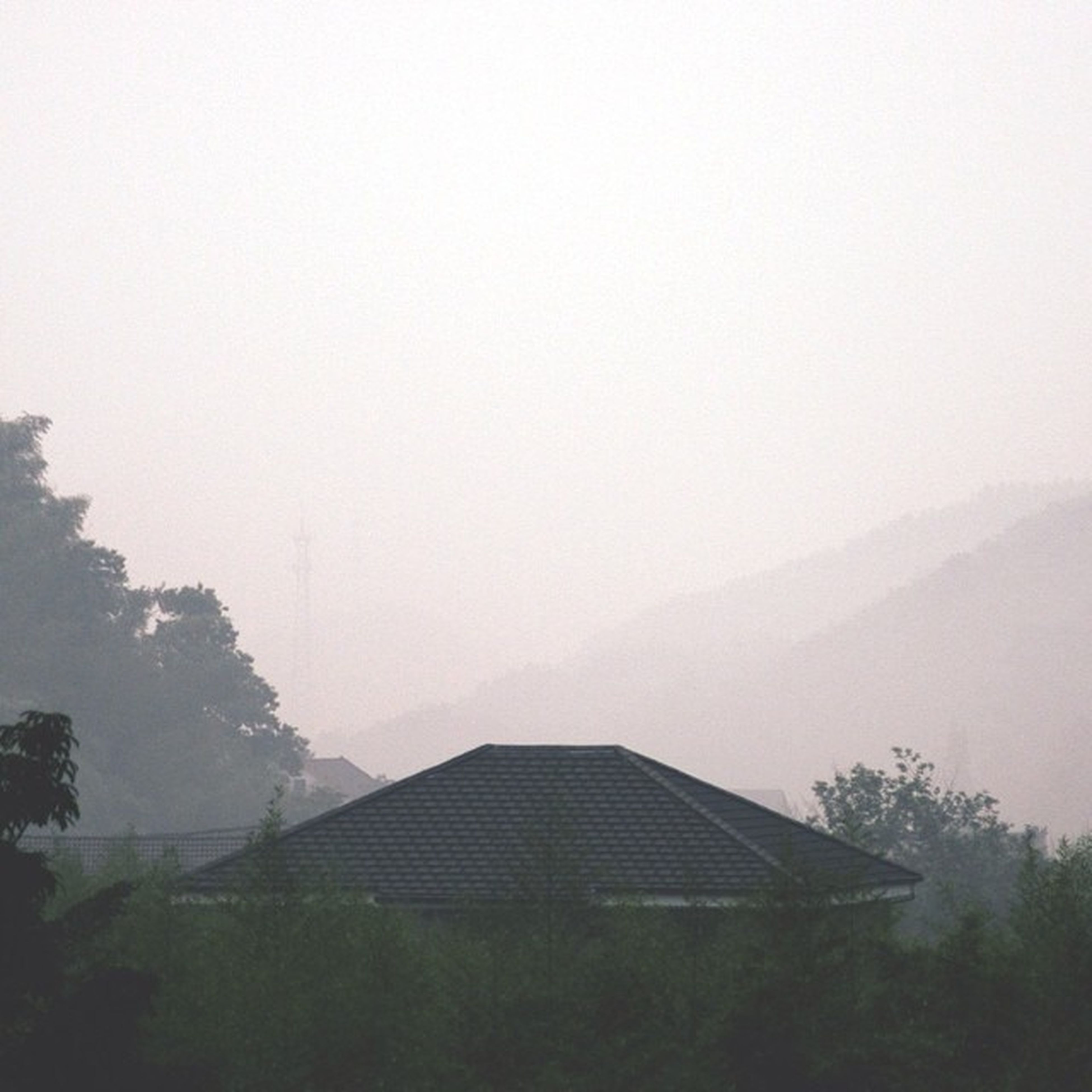 fog, foggy, built structure, architecture, building exterior, weather, copy space, mountain, house, tree, tranquility, nature, landscape, tranquil scene, sky, beauty in nature, scenics, day, no people