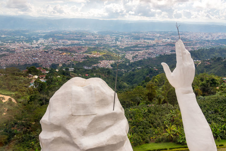 Head and hand of El Santisimo statue with Bucaramanga visible in the background Bucaramanga Building Catholic Cerro Christ Christianity City Cloud Clouds Colombia Ecoparque Elsantisimo Floridablanca Jesus Landmark Park Religion Santander Santisimo Sculpture Statue Structure Urban View White