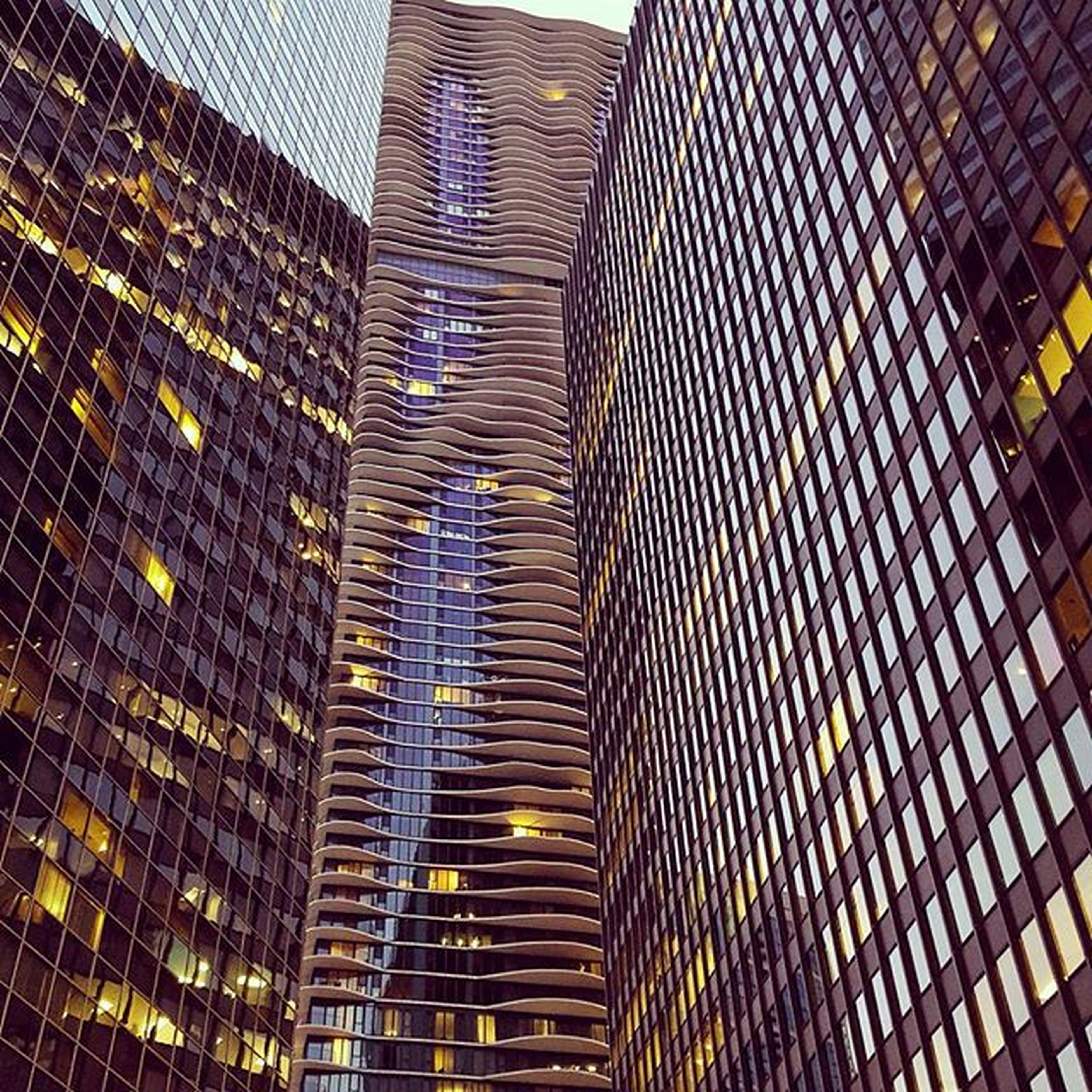 architecture, building exterior, built structure, city, skyscraper, modern, low angle view, office building, tall - high, tower, building, glass - material, window, reflection, pattern, no people, architectural feature, capital cities, city life, day