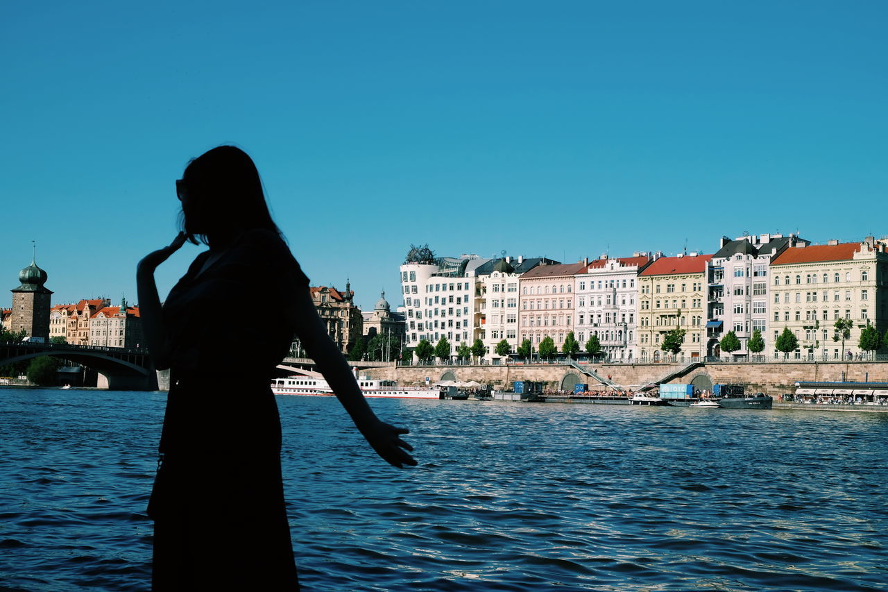 Martyna dancing with a Dancing House by the Riverside // Architecture Building Exterior Built Structure Real People Water Clear Sky Waterfront One Person Outdoors Day Standing Nautical Vessel City Sky People FUJIFILM X-T10 XF18-55mmF2.8-4 R LM OIS F/8.9 Iso 200 Rear View Lifestyles 1/420 Sec Women via Fotofall