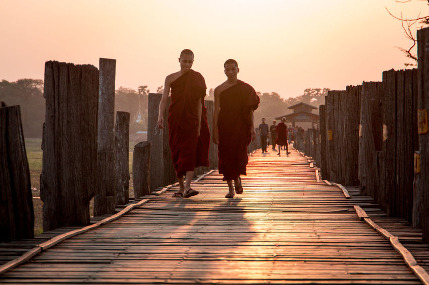 Buddhist Monks stroll across Ubein Bridge in Myanmar as the sun rises over the horizon and washes everything in a warm orange glow. See more: Instagram.com/LostBoyMemoirs BLOG: Lostboymemoirs.com ASIA Backpacking Bridge Bridge - Man Made Structure Buddhism Buddhist Burma Dusk Glow Haze Low Angle View Monk  Monkey Myanmar Old Orange Perspective Reflection Sun Sunrise Sunrise_Collection Travel Ubeinbridge UNESCO World Heritage Site Walking Breathing Space