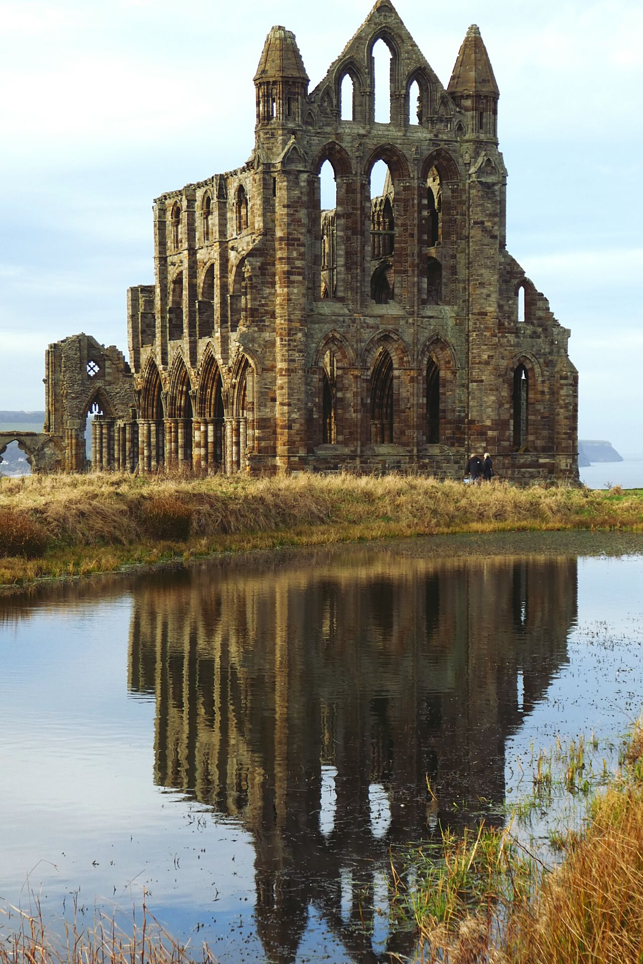 Dramatic and evocative, Whitby Abbey commands the town from its windy North Yorkshire headland. You can see the ruins from several miles distant. Up close, they are even more magnificent : the glorious stonework, eroded by the salty air is still as beautifully detailed as it would have been in the 13th century. The abbey stands stark against the Yorkshire sky and North Sea waves and one can see why it became the inspiration for Bram Stokers dracula! ... Reflection Architecture Built Structure Whitby Abbey Building Exterior Ruin Dissolution Of The Church Henry VIII Travel Destinations History Water Outdoors Sky No People Cultures Distant Sea Magnificent Ancient Architecture 657 A.d. Spooky Atmosphere
