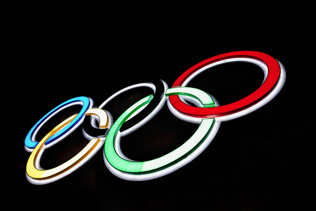 Olympic Rings - Illuminated Neon Sign Black Background Circle Close-up Commercial Sign Competition Competitive Sport Illuminated Logo Multi Colored Neon Neon Lights Night No People Olympic Olympic Games Olympic Rings Olympics Rings Sign Sport Sports Symbol Tradition Victory Winner