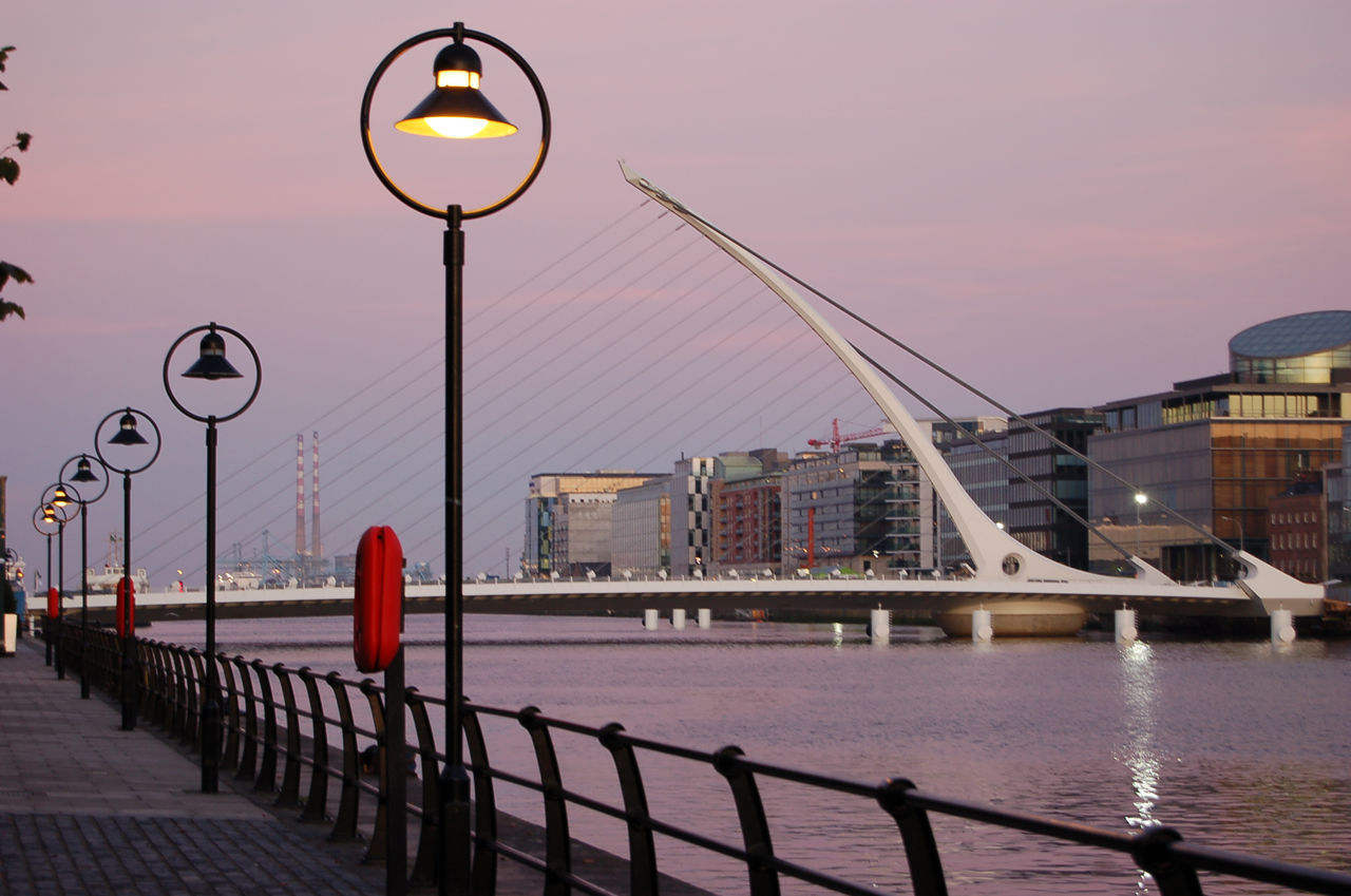 architecture, built structure, city, bridge - man made structure, building exterior, river, street light, outdoors, water, transportation, sky, no people, sunset, illuminated, day
