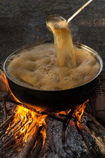 stirring a pot of pekmez (apple molasses) Apples Boiling Cooking Fire Flames Foam Kazan Ladle Making Molasses Pear Pekmez Pekmez Yapimi Pot Stirring Turkey Wood