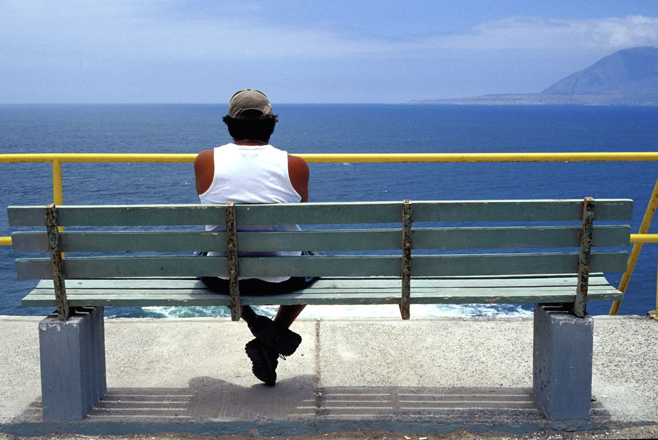 Adult Antofagasta Beauty In Nature Bench Blue Blue Color Chile Day Full Length Horizon Over Water Nature One Person Outdoors Pacific Ocean People Railing Rear View Sea Seat Sky Sunlight Water Wooden Bench Yellow Yellow Color