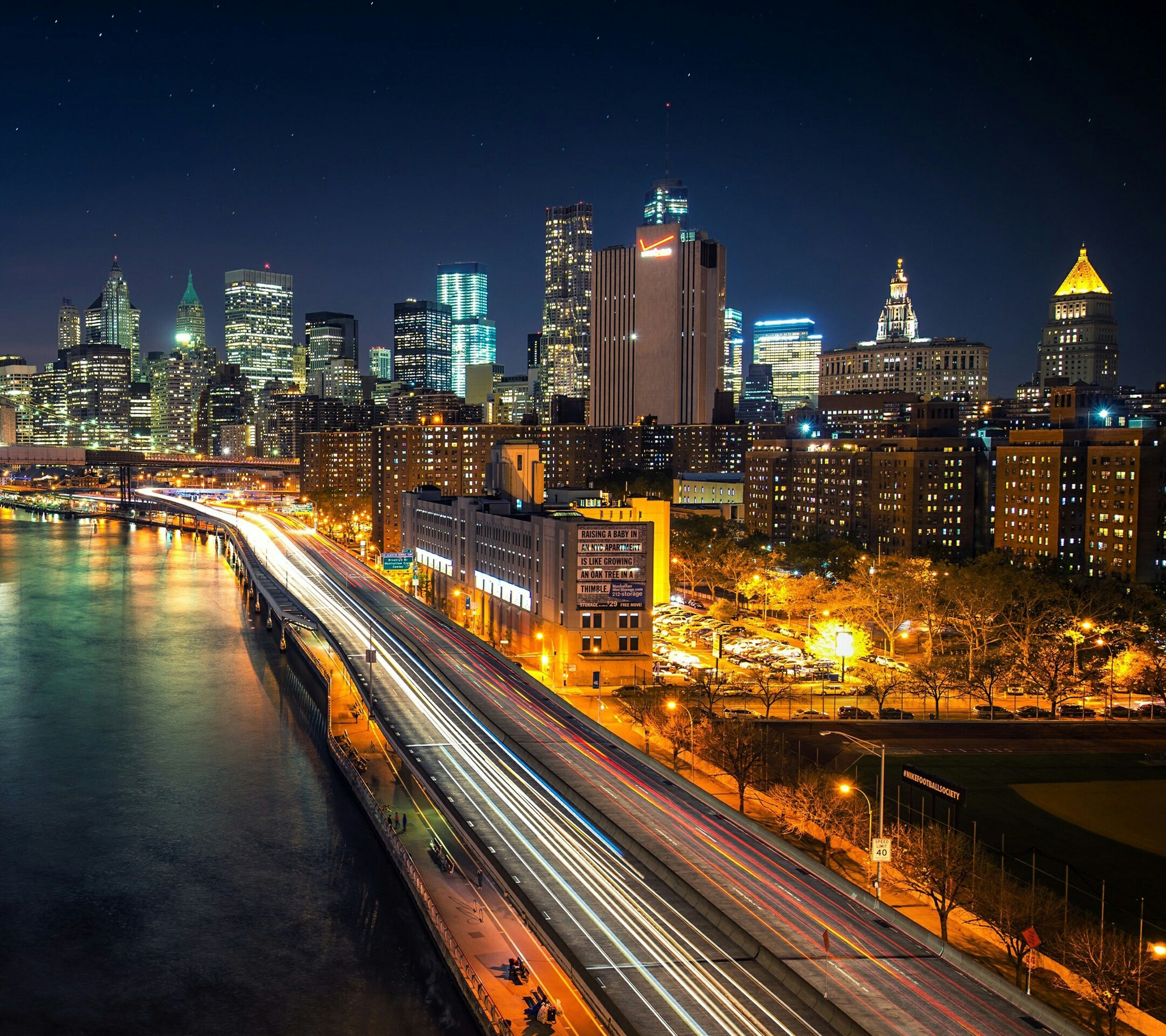 illuminated, night, city, building exterior, architecture, built structure, cityscape, skyscraper, light trail, long exposure, transportation, modern, city life, river, high angle view, water, tower, tall - high, office building, sky