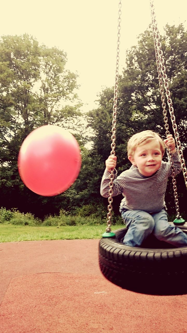 swing, childhood, playground, playing, outdoor play equipment, rope swing, innocence, fun, one person, park - man made space, full length, happiness, smiling, leisure activity, tree, sitting, ride, hanging, outdoors, carousel, sky, day, people