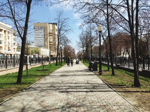 Bare Tree Tree Built Structure Architecture City Day Real People The Way Forward Walking Building Exterior Outdoors City Life Men Branch Sky Women Nature Adult People