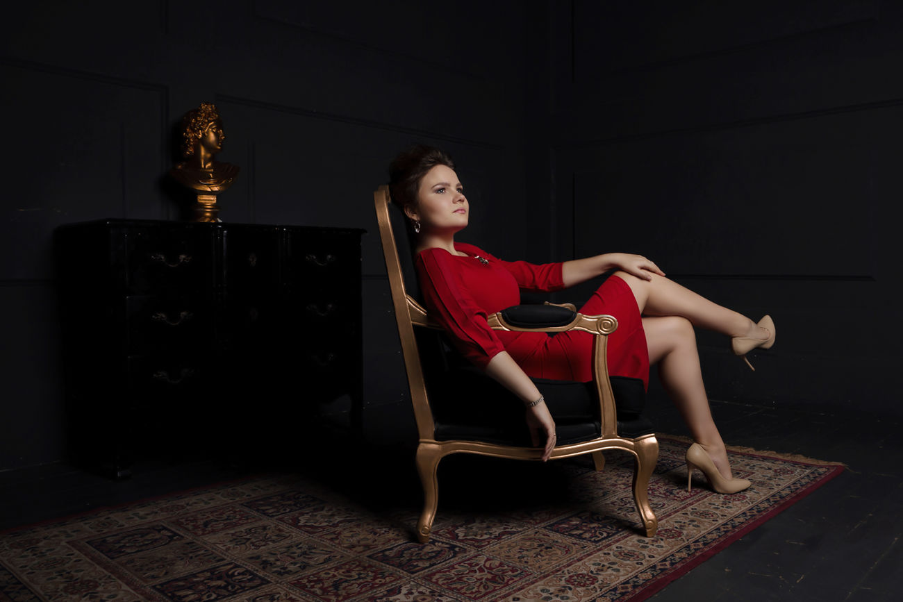 girl in red dress sittng in dark room in chair Beautiful Woman Boss Chair Dark Full Length Golden High Heels Indoors  Legs Crossed At Knee Lifestyles One Person People Portrait Red Dress Relax Relaxation Seat Sitting Strong Woman The Portraitist - 2017 EyeEm Awards Young Adult Young Women