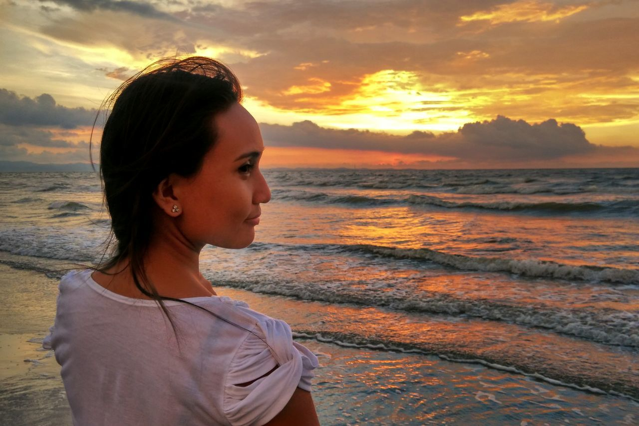 Young Woman Overlooking Calm Sea At Sunset