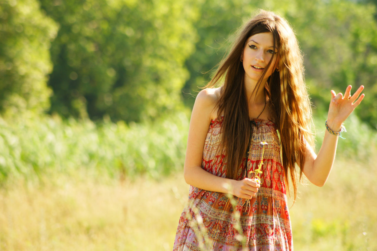 Beautiful Woman Standing On Grassy Field
