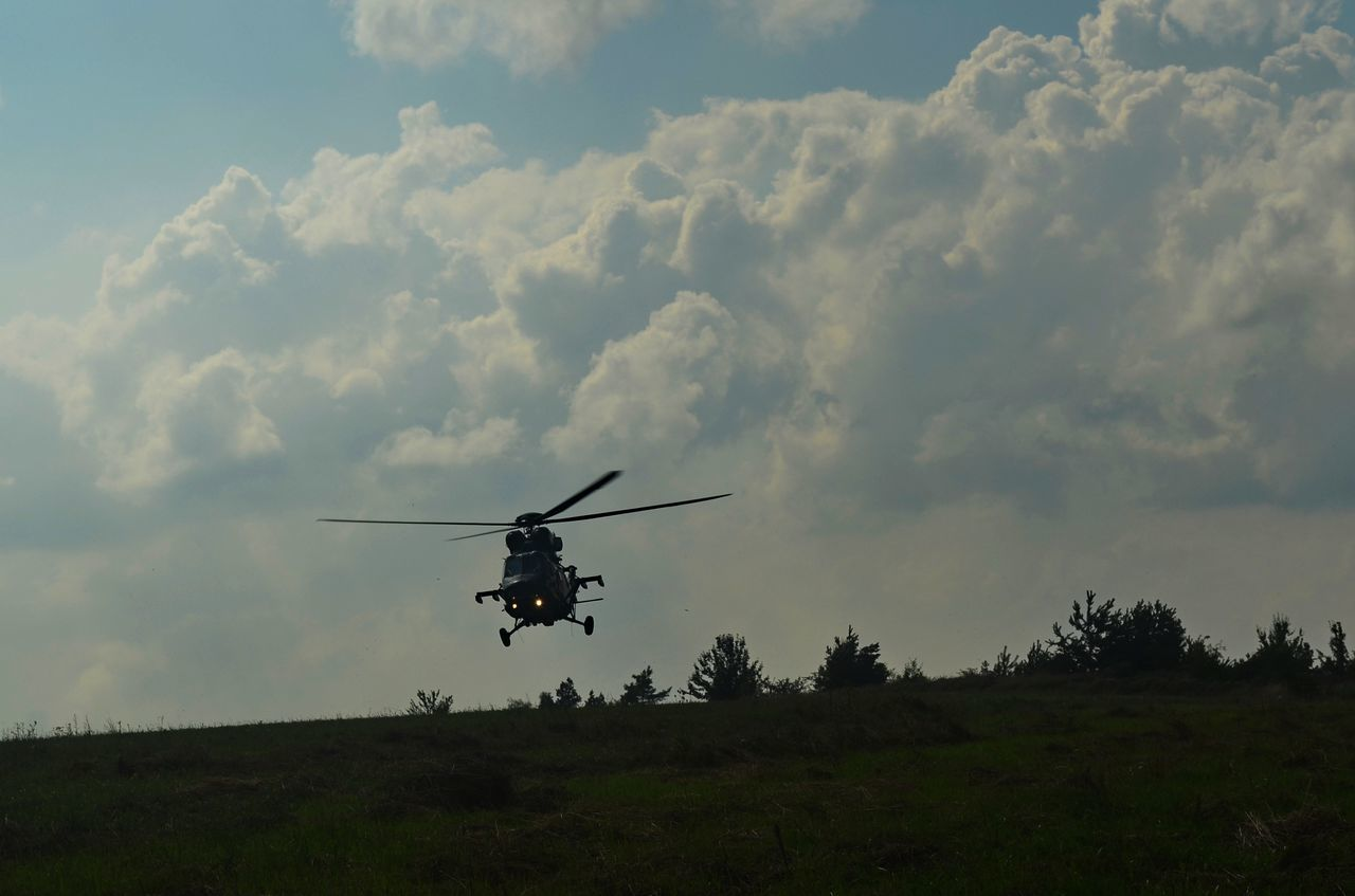 Helicopter Flying Over Field Against Cloudy Sky