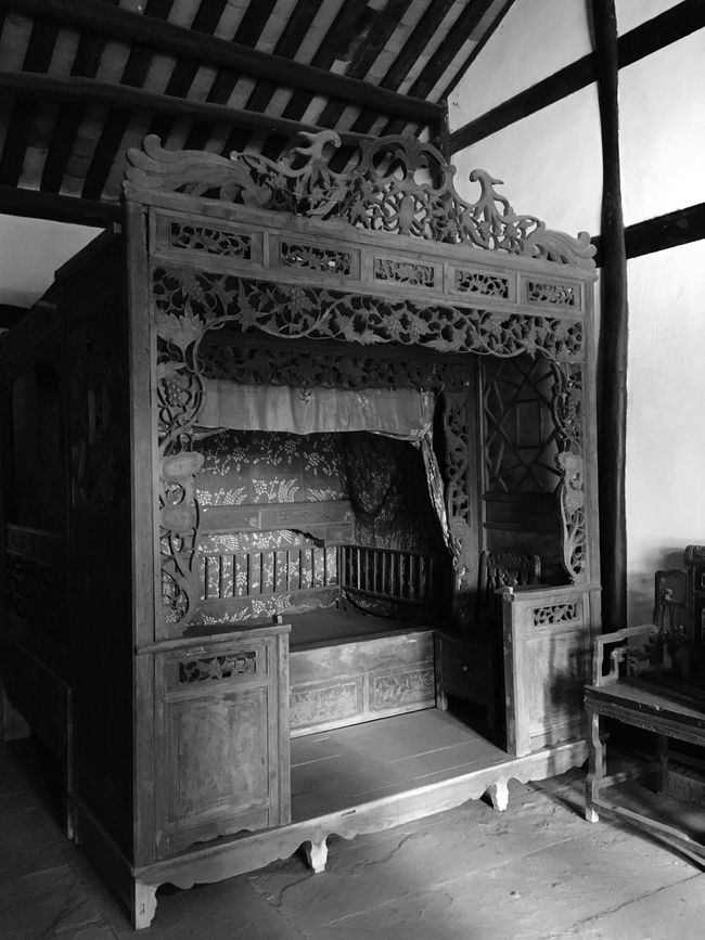 A great man deng xiaoping at the head of a bed of carve patterns or designs on woodwork.