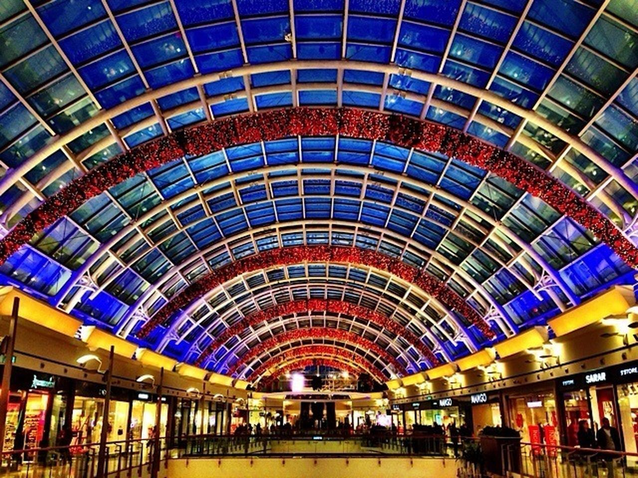 architecture, built structure, ceiling, modern, shopping mall, city, transportation building - type of building, arch, illuminated, city life, architectural feature, interior, travel destinations, building, architectural column, day, repetition, no people, diminishing perspective