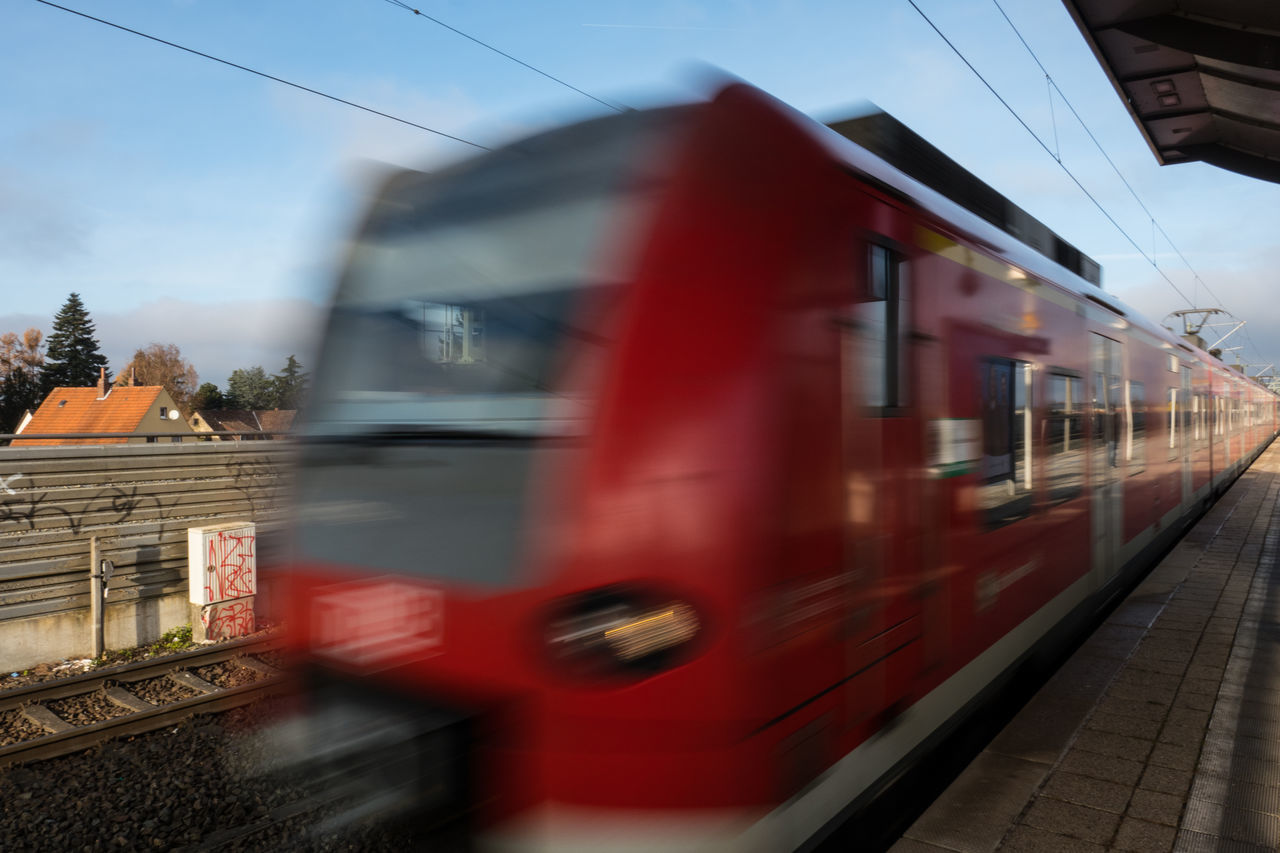 A red train in motion leaves the station Blurred Motion Day In Motion Motion No People Outdoors Red Speed Speeding Train Train In Motion