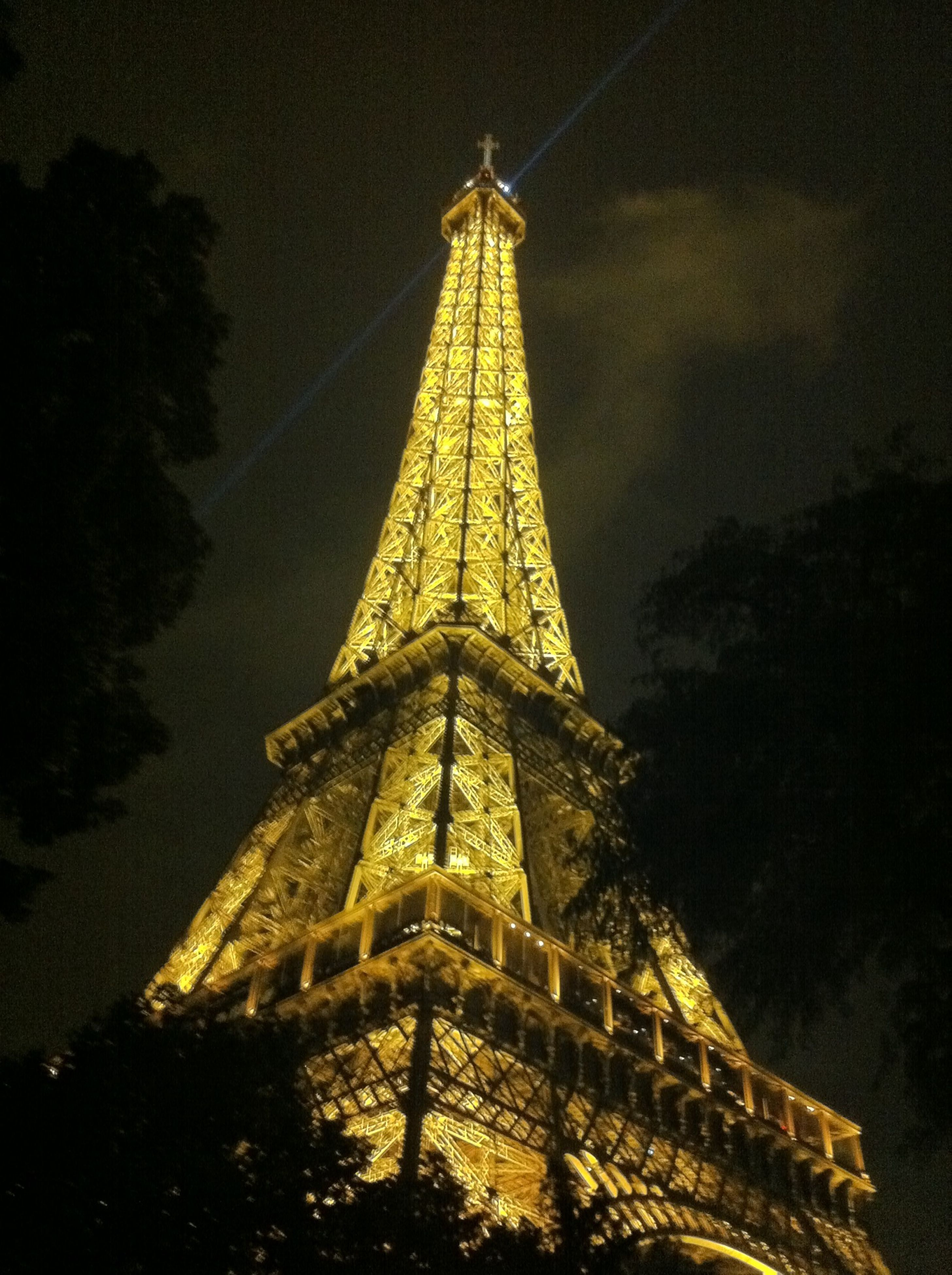 low angle view, built structure, sky, architecture, tower, tall - high, eiffel tower, illuminated, night, travel destinations, famous place, international landmark, tree, tourism, dusk, travel, capital cities, outdoors, metal, no people