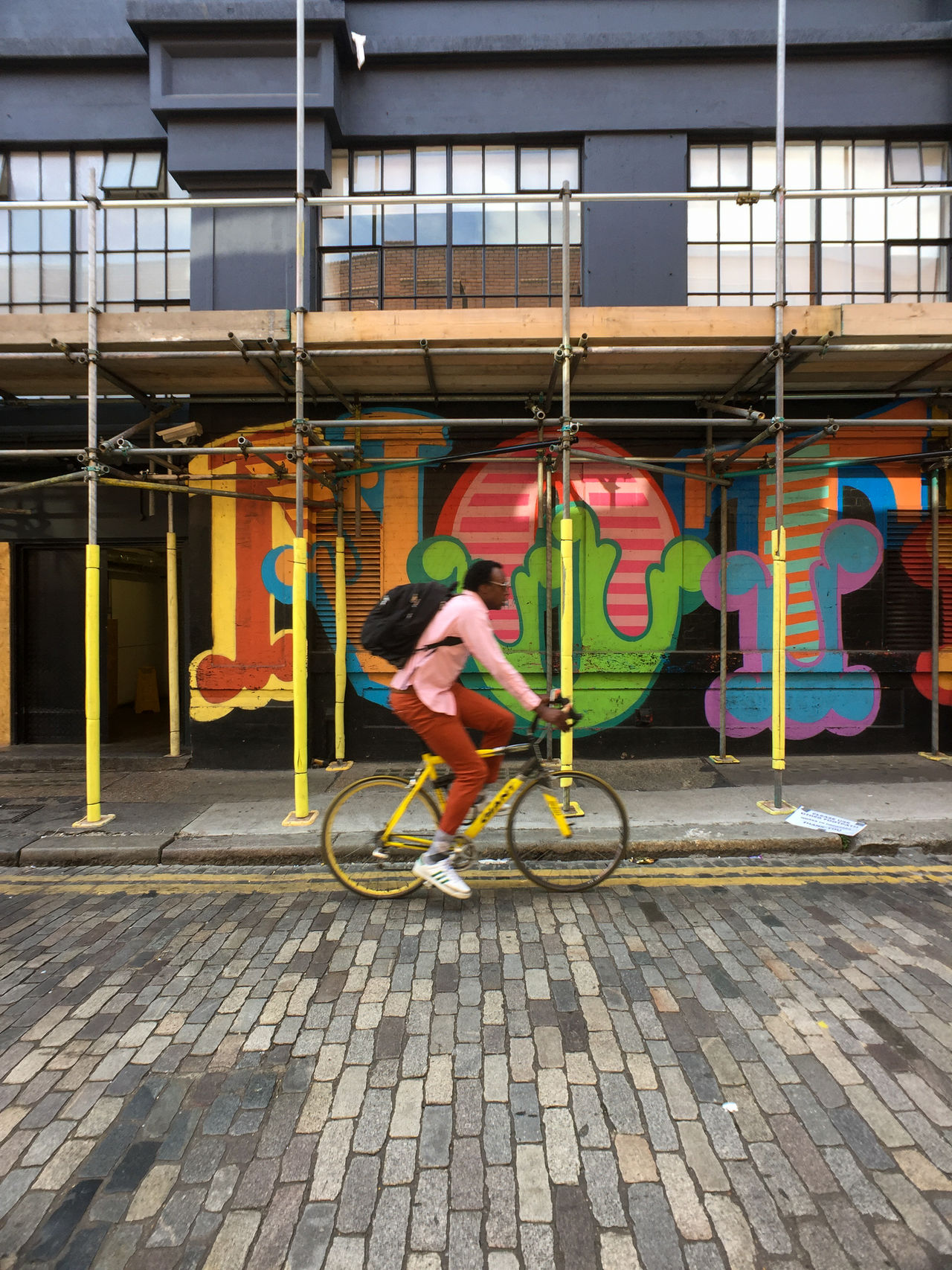 A man bicycles down a colorful street in the Shoreditch neighborhood of East London. Graffiti London Scaffolding Shoreditch Adult Architecture Bicycle Building Exterior Built Structure City Day Editorial  Men One Person Outdoors People Real People Stone Material Street Photography Streetphotography Transportation