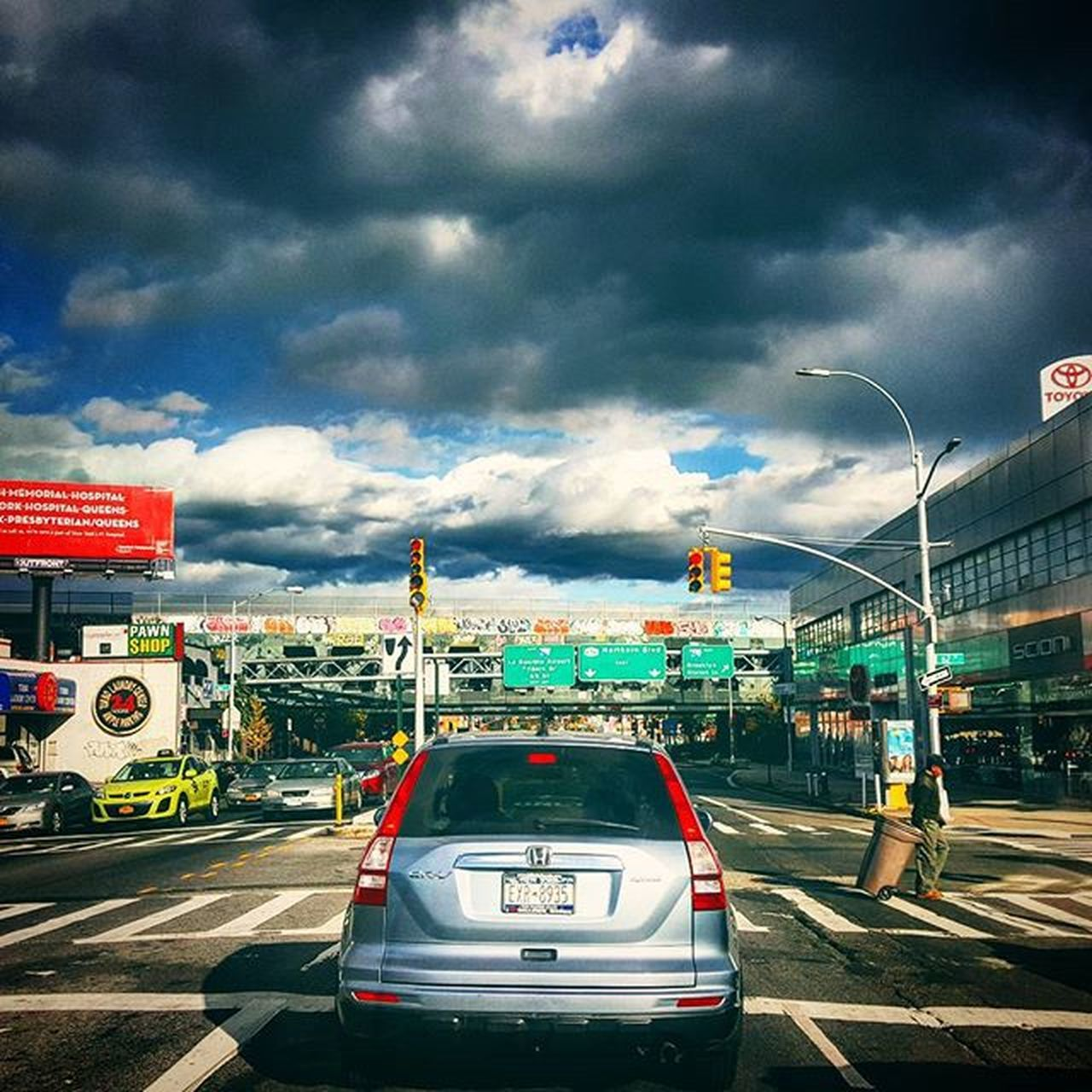 cloud - sky, transportation, car, sky, mode of transport, land vehicle, architecture, built structure, text, building exterior, outdoors, day, road, city, real people