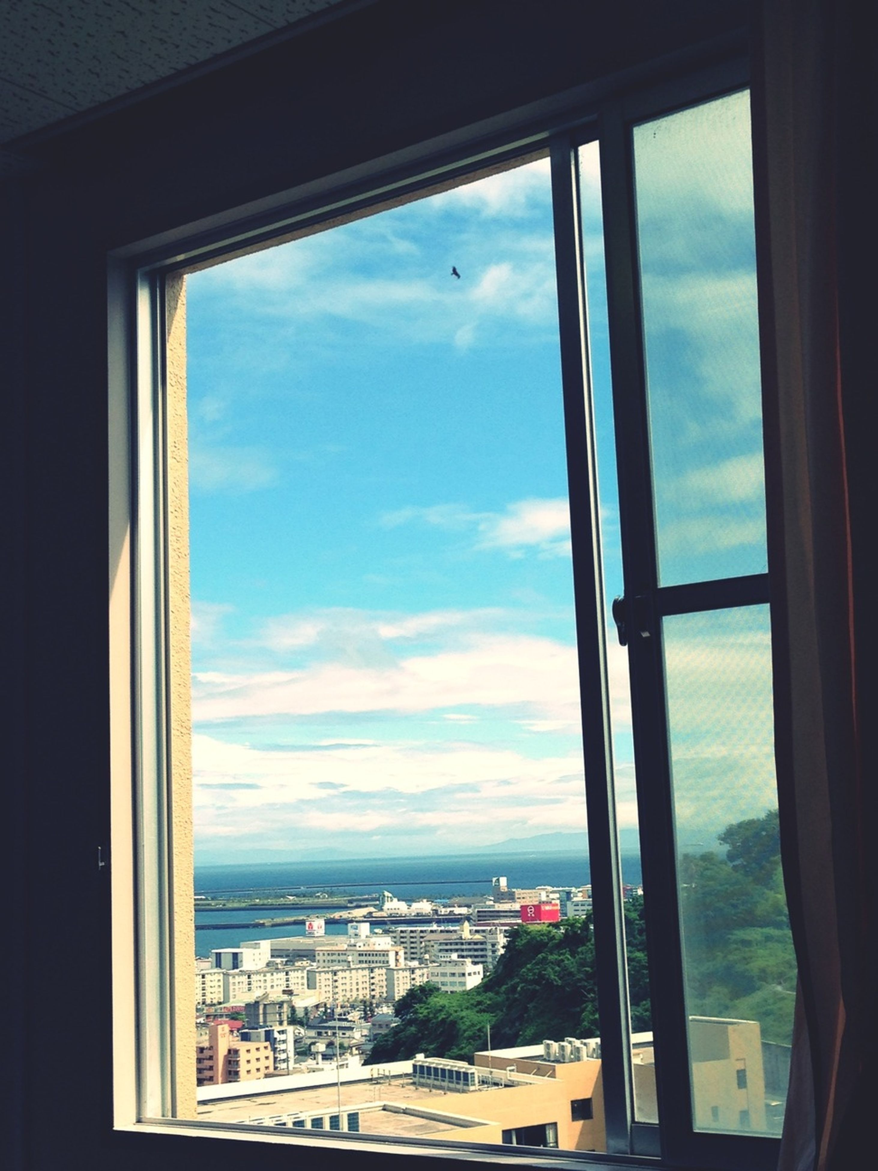 window, indoors, transparent, glass - material, sky, architecture, built structure, sea, looking through window, vehicle interior, cityscape, cloud - sky, city, transportation, cloud, water, day, building exterior, house, glass