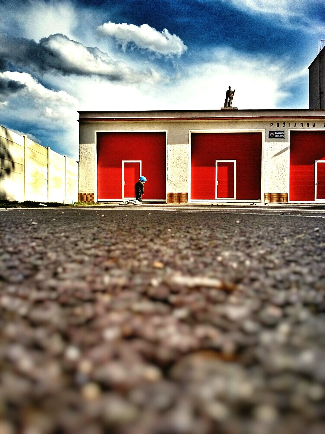 Here Belongs To Me Fire Station Red Gate Saint Florent Statue Patron Boy Blue Helmet Kids Sports Red Door Sky And Clouds Light And Shadow Slovakia Village Asphalt Concrete Wall