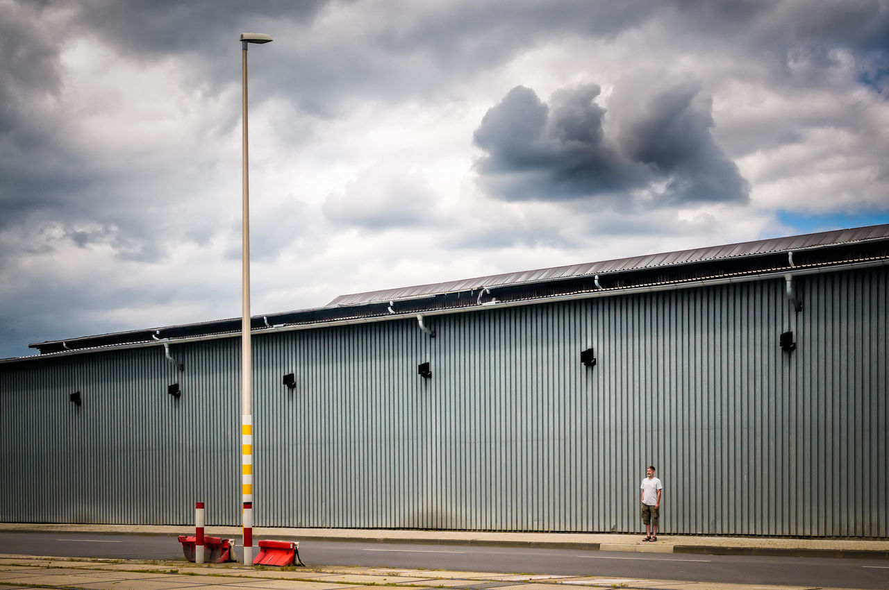 Man Standing On Footpath By Factory Against Cloudy Sky