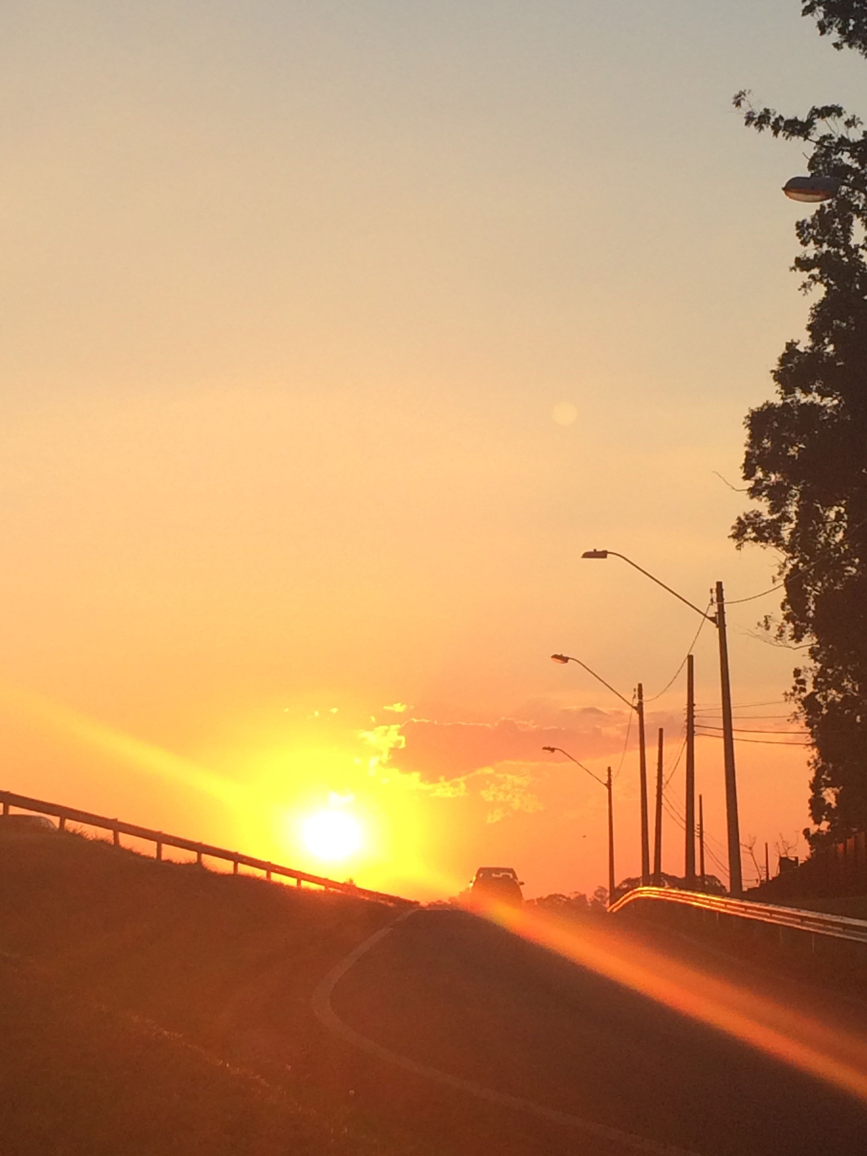 sunset, sun, street light, orange color, road, cloud, tree, scenics, tranquil scene, sky, tranquility, solitude, moody sky, beauty in nature, sunbeam, outdoors, dramatic sky, the way forward, surface level, nature, majestic, atmospheric mood, long, remote, outline, atmosphere