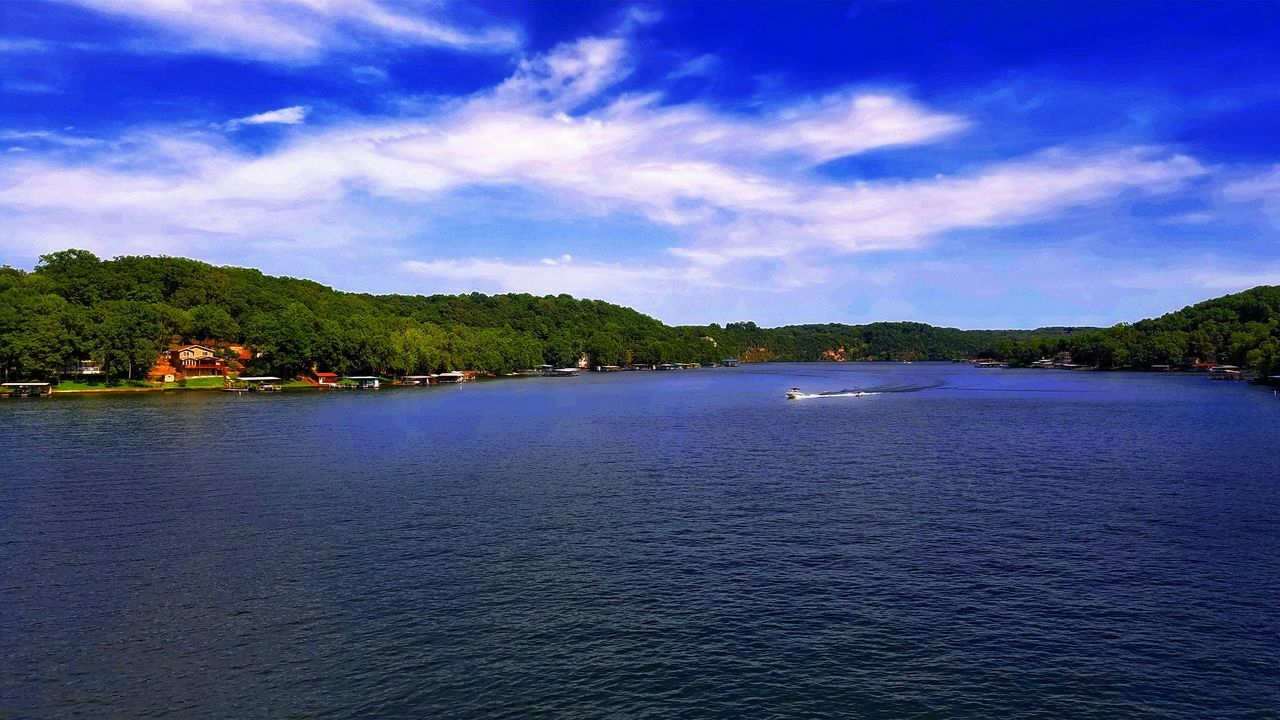 water, sky, nature, waterfront, cloud - sky, scenics, blue, outdoors, beauty in nature, tranquil scene, tree, river, no people, tranquility, architecture, day, built structure, nautical vessel, wake, view into land