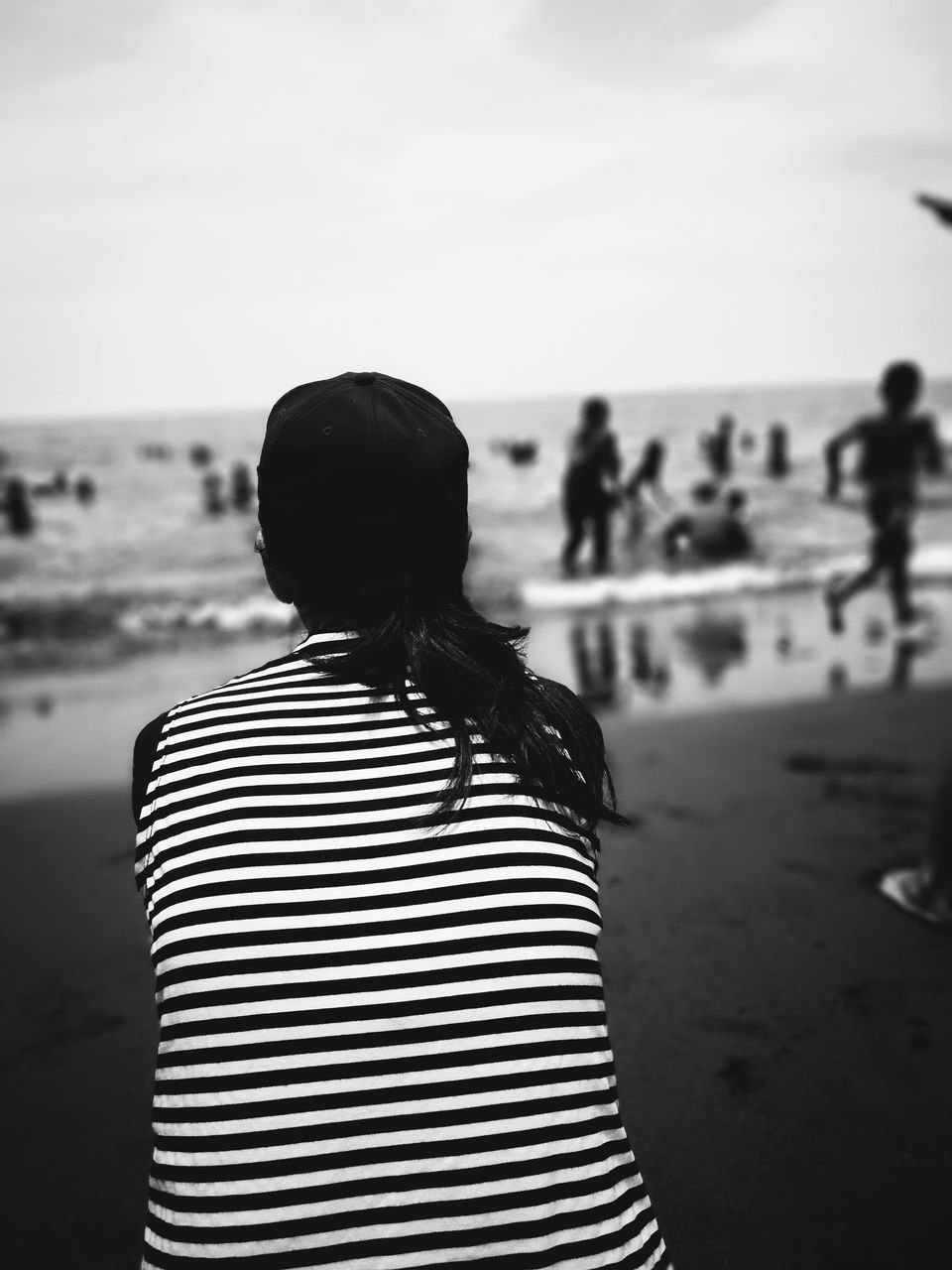 rear view, real people, beach, striped, sea, focus on foreground, sand, women, nature, standing, leisure activity, water, vacations, outdoors, horizon over water, scenics, lifestyles, tranquility, one person, day, sky, beauty in nature, adult, people