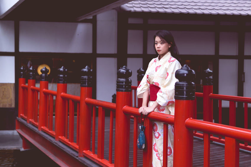 Architecture Beautiful Woman Built Structure Casual Clothing Day Front View Full Length Kimono Leisure Activity Lifestyles One Person Outdoors Railing Real People Red Smiling Standing Walking Young Adult Young Women