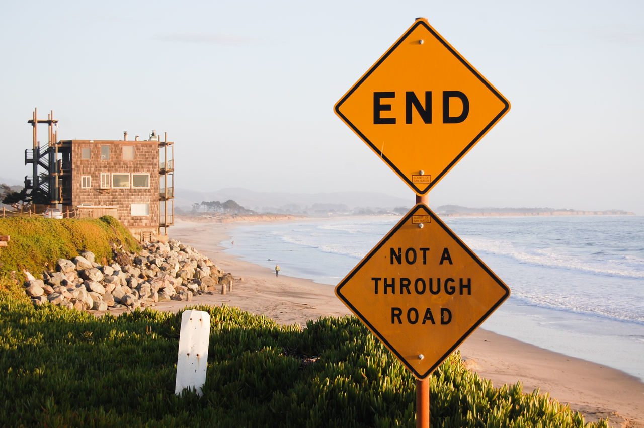 Close-Up Of Road Sign Against Beach