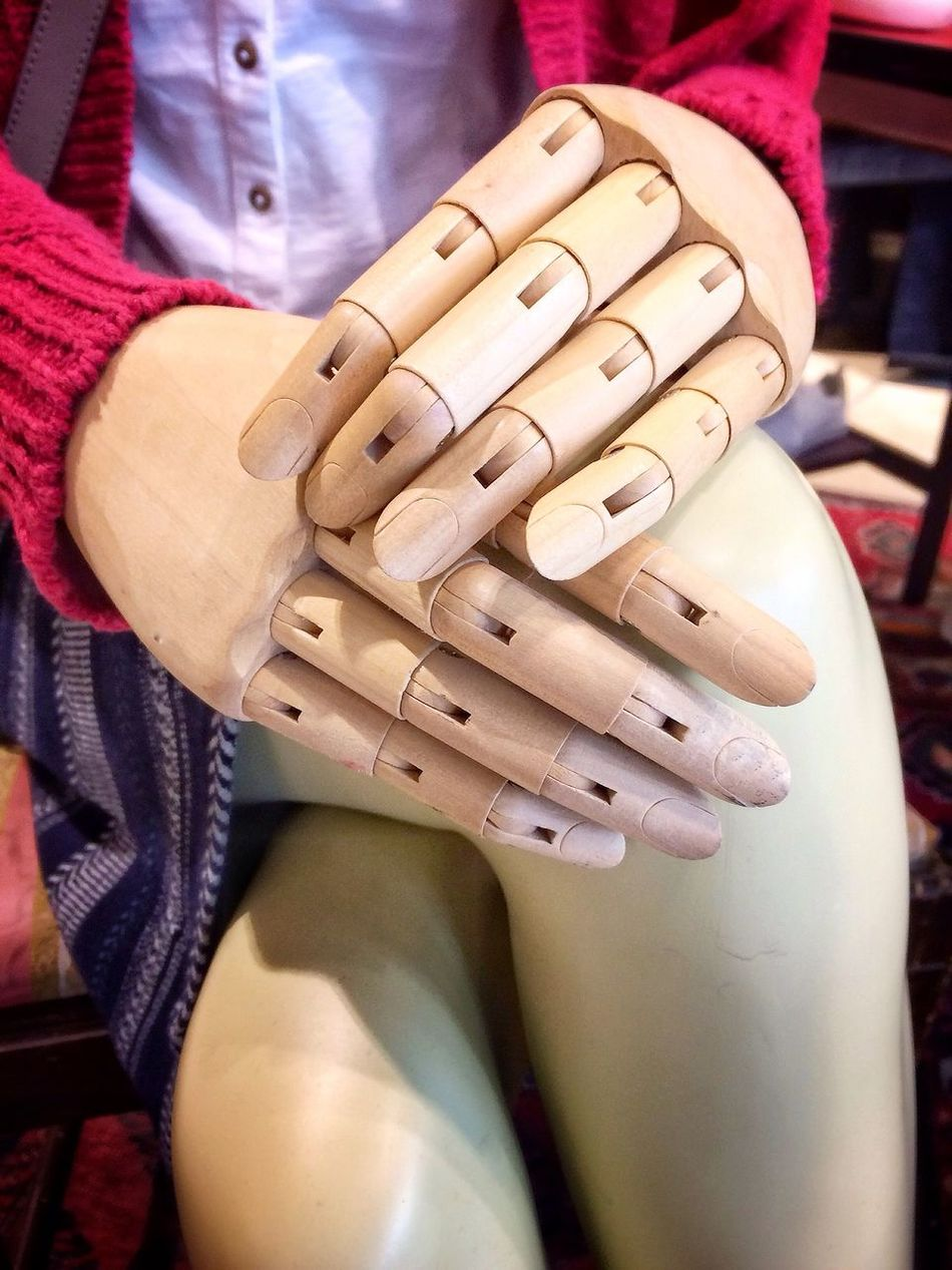 Wooden hands and fingers resting on female legs and representing arthritis and joints. Human Hand Hands Wooden Wood Fingers Digits Joints Female Woman Old Arthritis Pain Articulated Mannequin Dummy Crossed Legs Sitting Closeup One Person Adult Human Body Part People Women Close-up Limbs