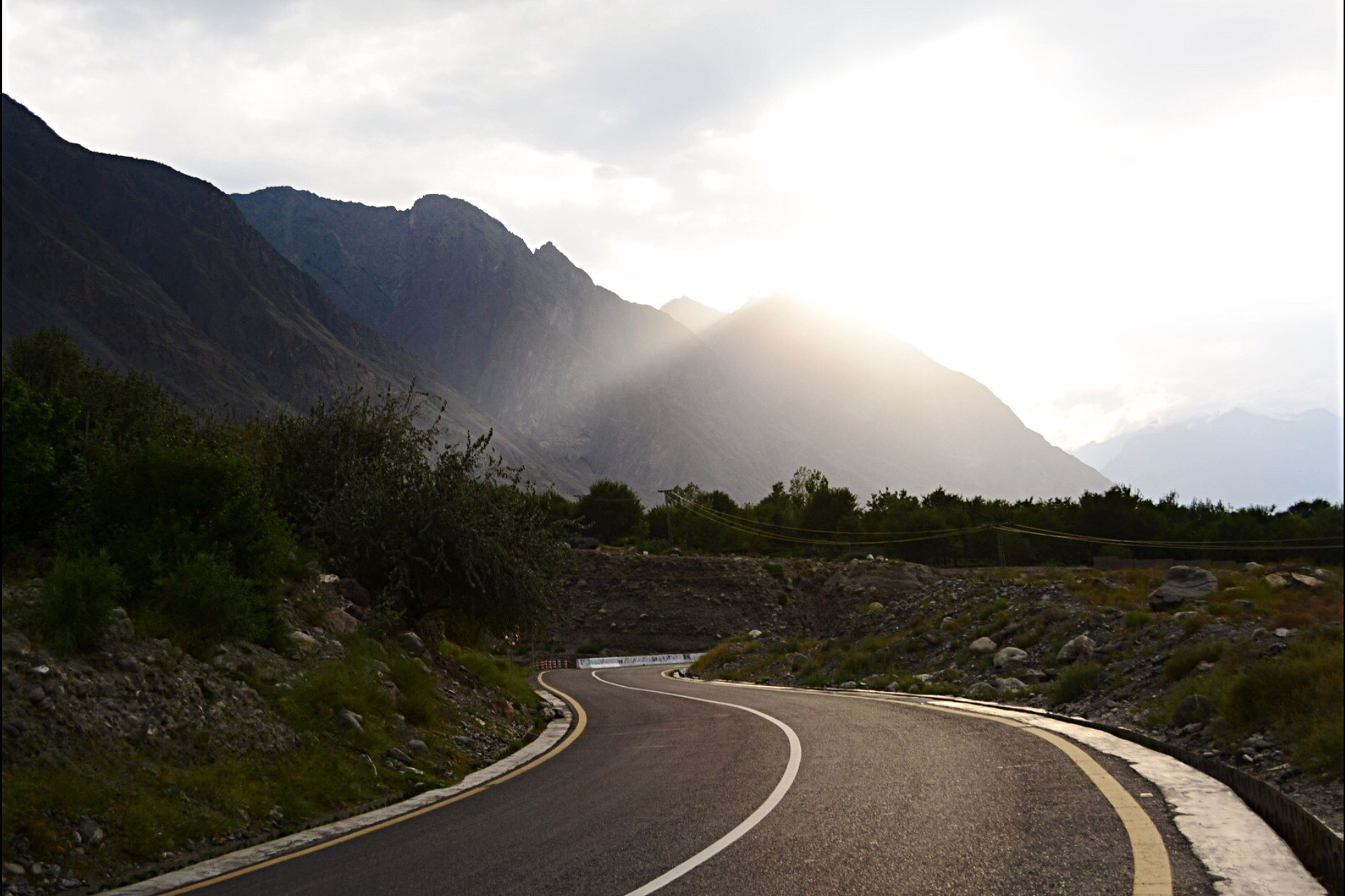 mountain, road, transportation, the way forward, tranquil scene, sunlight, landscape, tree, tranquility, scenics, sky, mountain range, sunbeam, beauty in nature, curve, sun, nature, non-urban scene, sunny, day, country road, remote, lens flare, outdoors, cloud - sky, majestic, countryside, green color, empty road