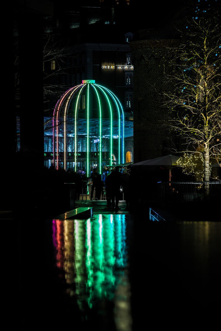 Reflection Of Illuminated Decoration By Buildings In Water