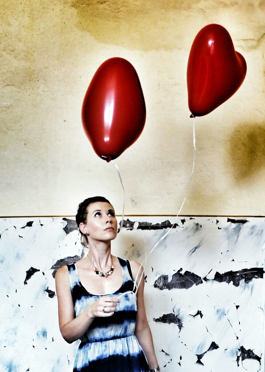 Young woman holding red helium balloons at home