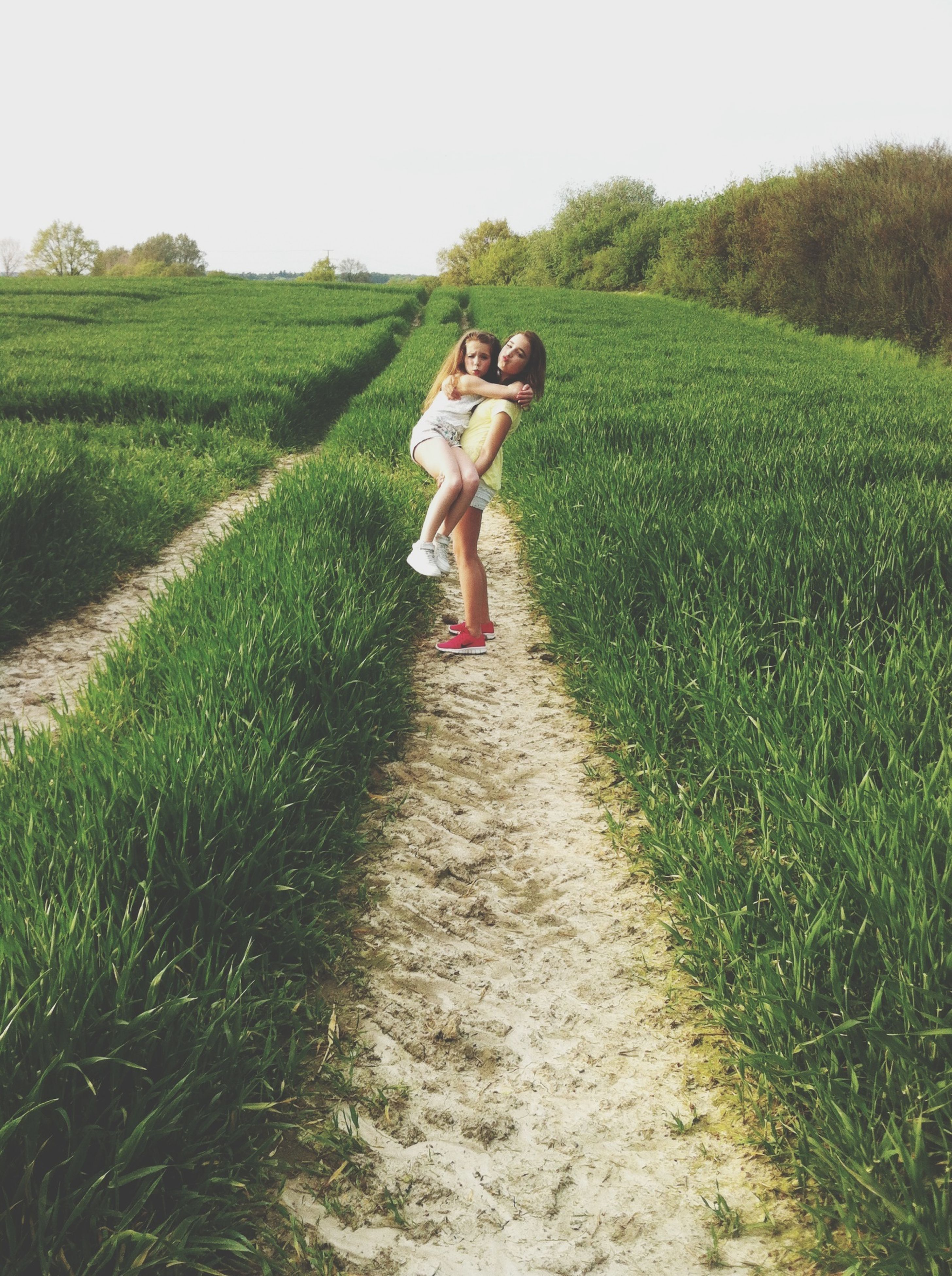 grass, full length, lifestyles, leisure activity, field, casual clothing, childhood, green color, grassy, growth, walking, boys, elementary age, girls, landscape, agriculture, rural scene, rear view