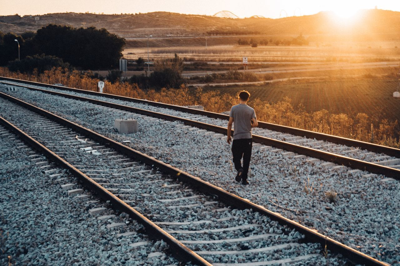 Railroad Track Rail Transportation Transportation One Man Only Outdoors One Person Sunset Sunlight Adult Only Men Nature Full Length Adventure Adults Only People Day Sky